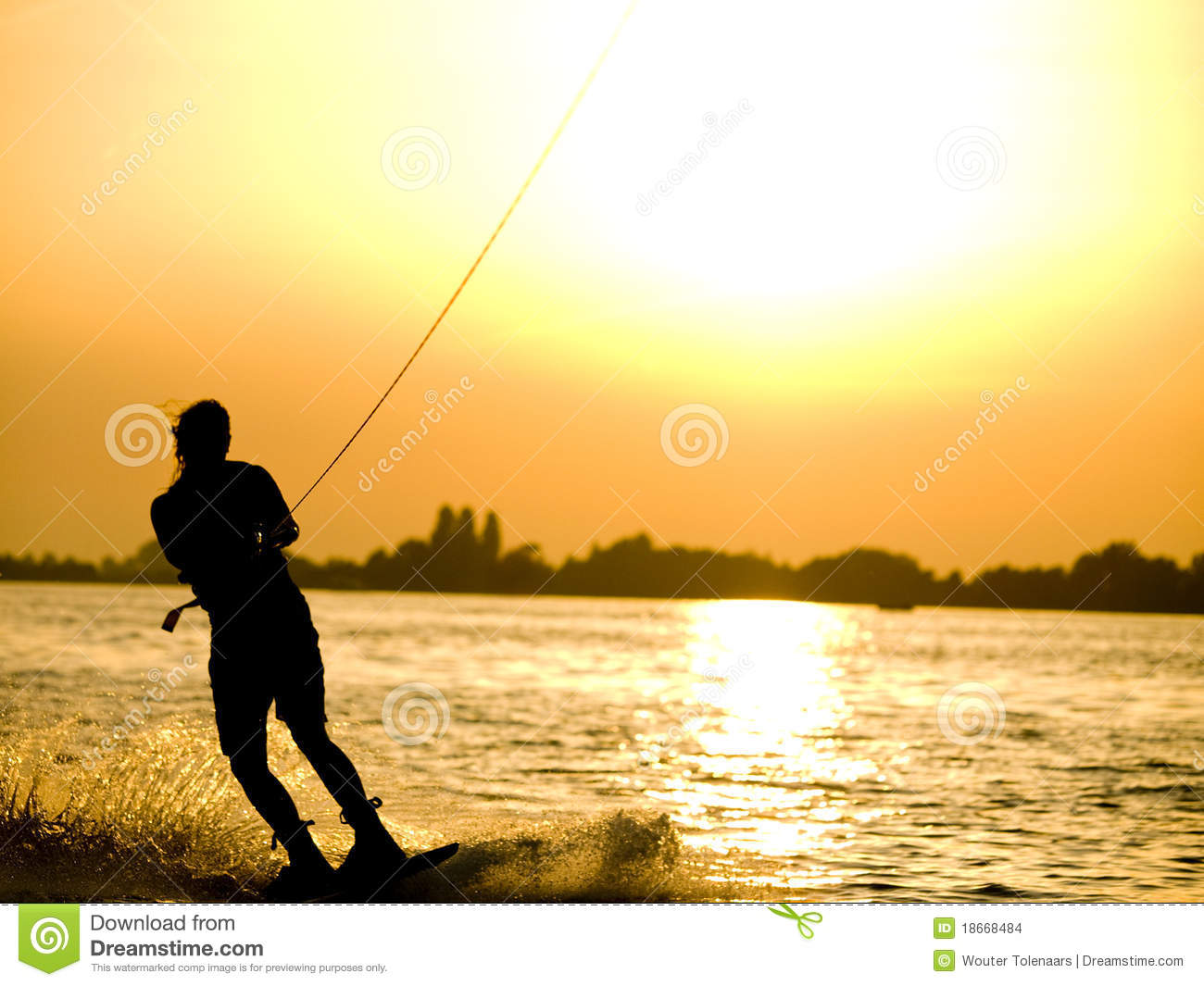 Girl is wakeboarding on a lake during a beautiful sunset.