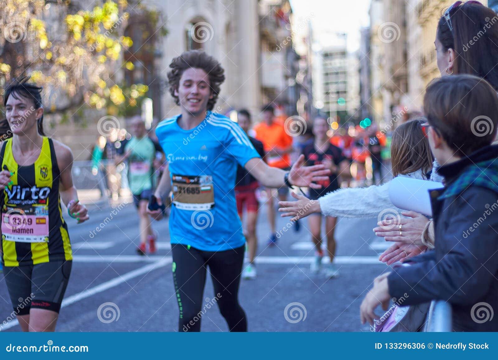 WALENCJA HISZPANIA, GRUDZIEŃ, - 2: Biegacze trząść ręki z osobami obecnymi przy XXXVIII Walencja maratonem na Grudniu 18, 2018 w