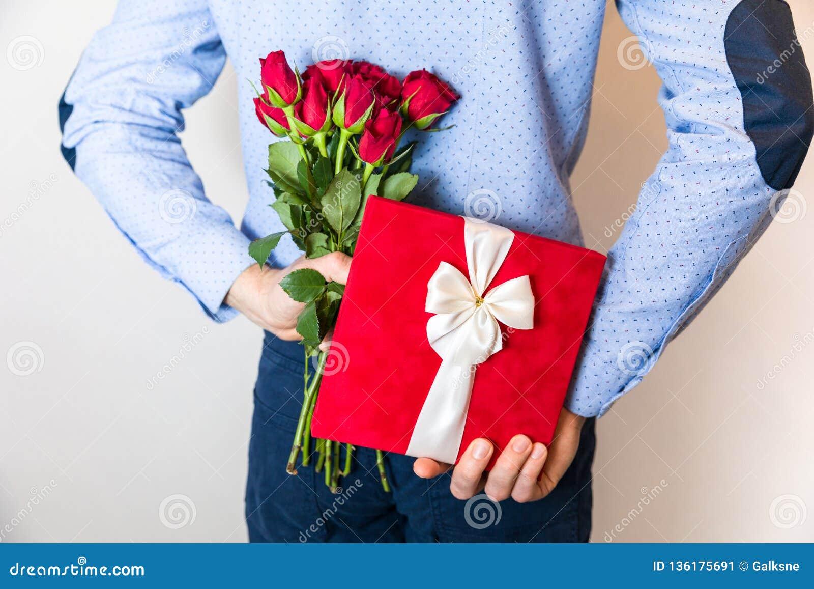 Walentynka dnia prezenta niespodzianka, mężczyzna chuje prezent i trzyma czerwieni róży bukiet