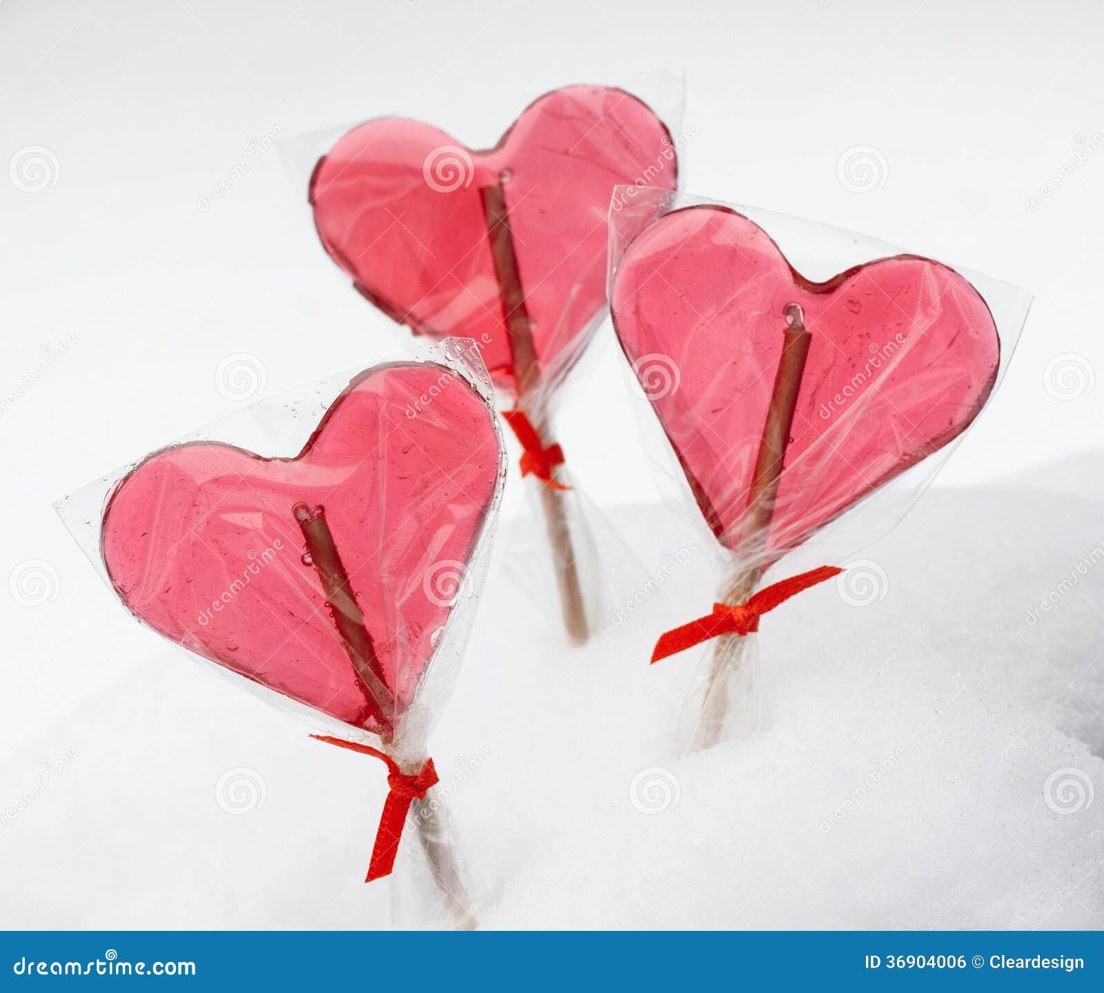 Walentynka dzień - czerwoni kierowi lizaki na śnieżnym tle