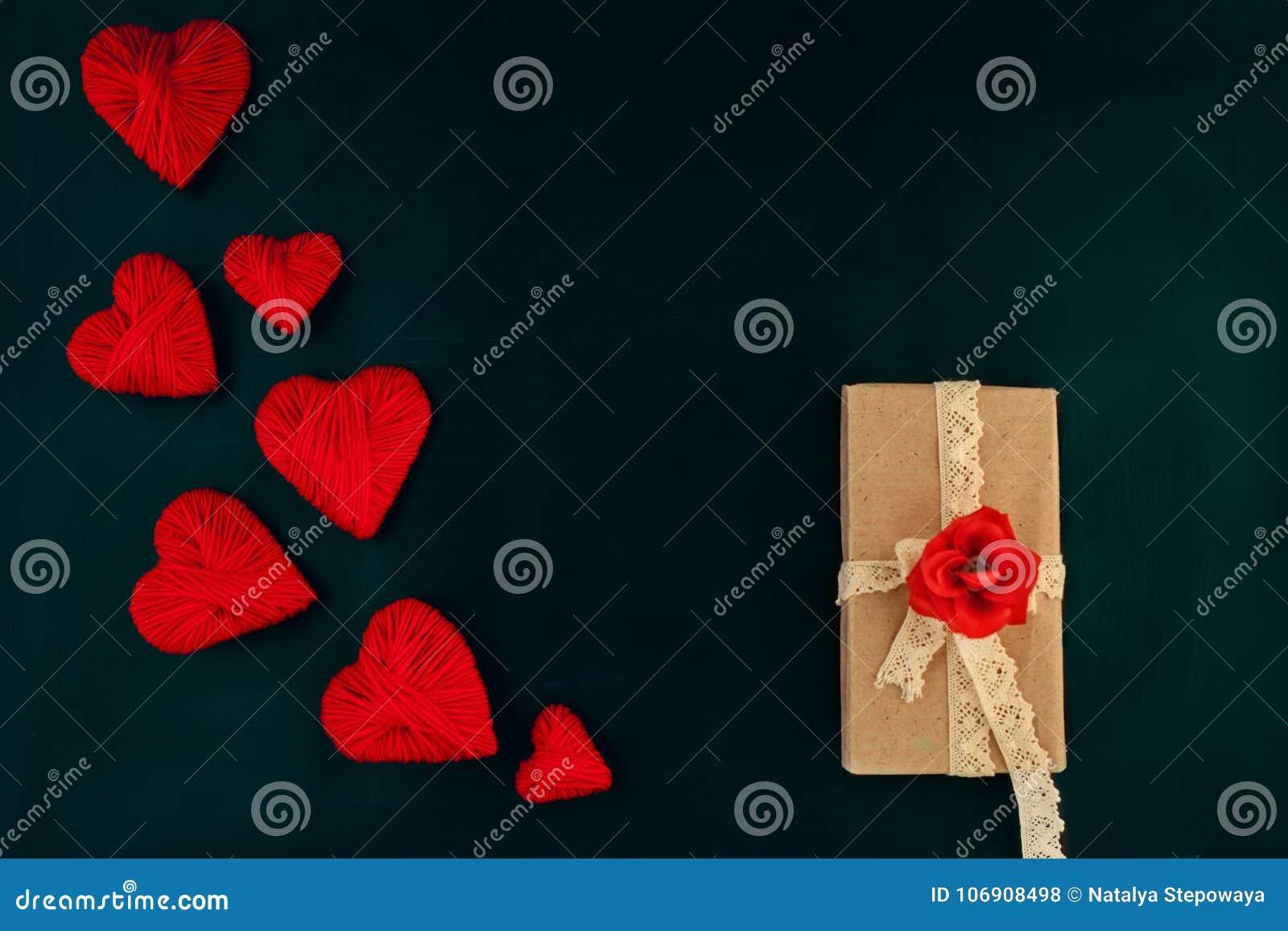 Walentynka dzień, czerwoni serca na ciemnym tle z prezentem, przestrzeń dla teksta