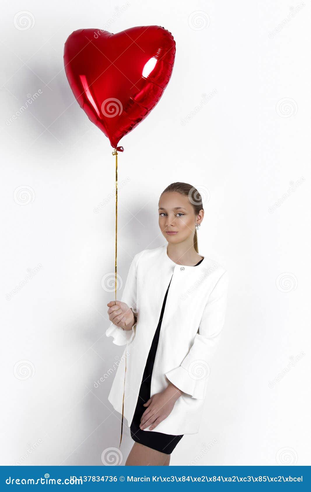 Walentynki piękna młoda dziewczyna, nastolatek z czerwonym lotniczego balonu portretem, odizolowywającym na tle
