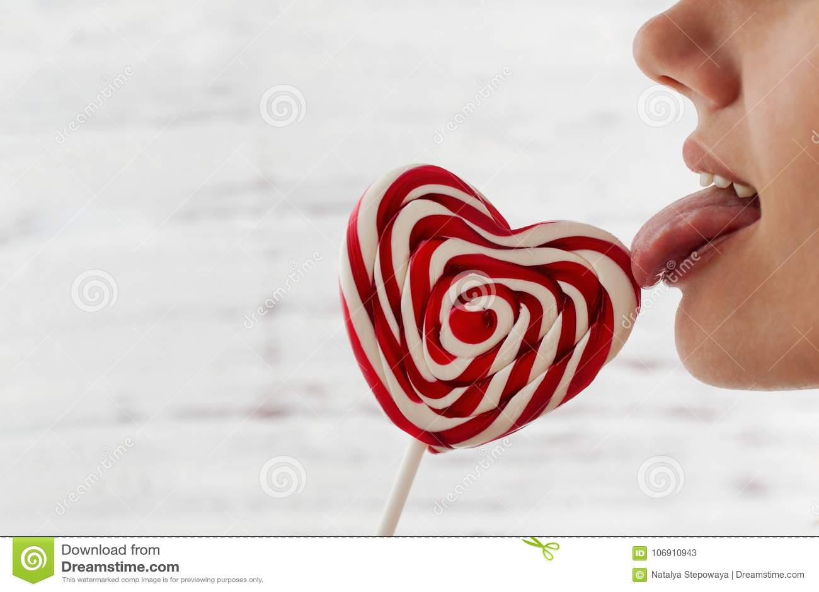 Walentynki ` s dzień, jęzoru oblizania czerwony cukierek w postaci serca, przestrzeń dla teksta