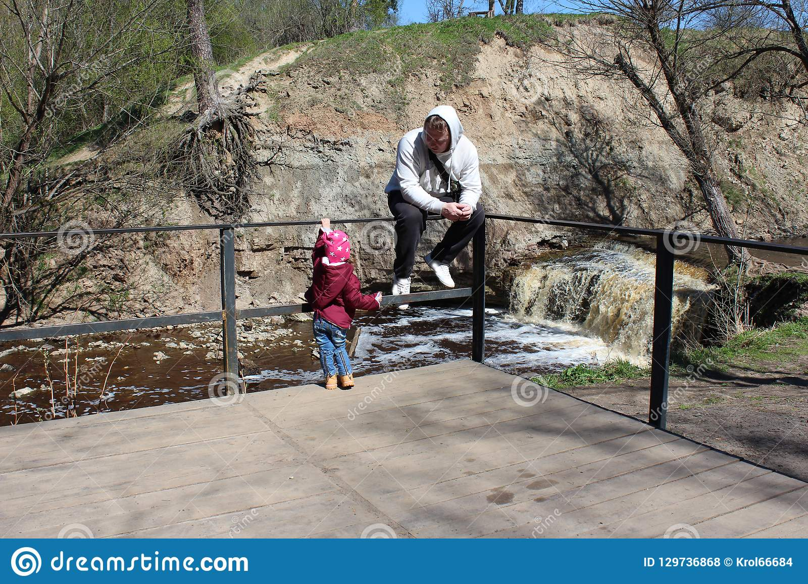 Walk daughter with his father in nature near the river.