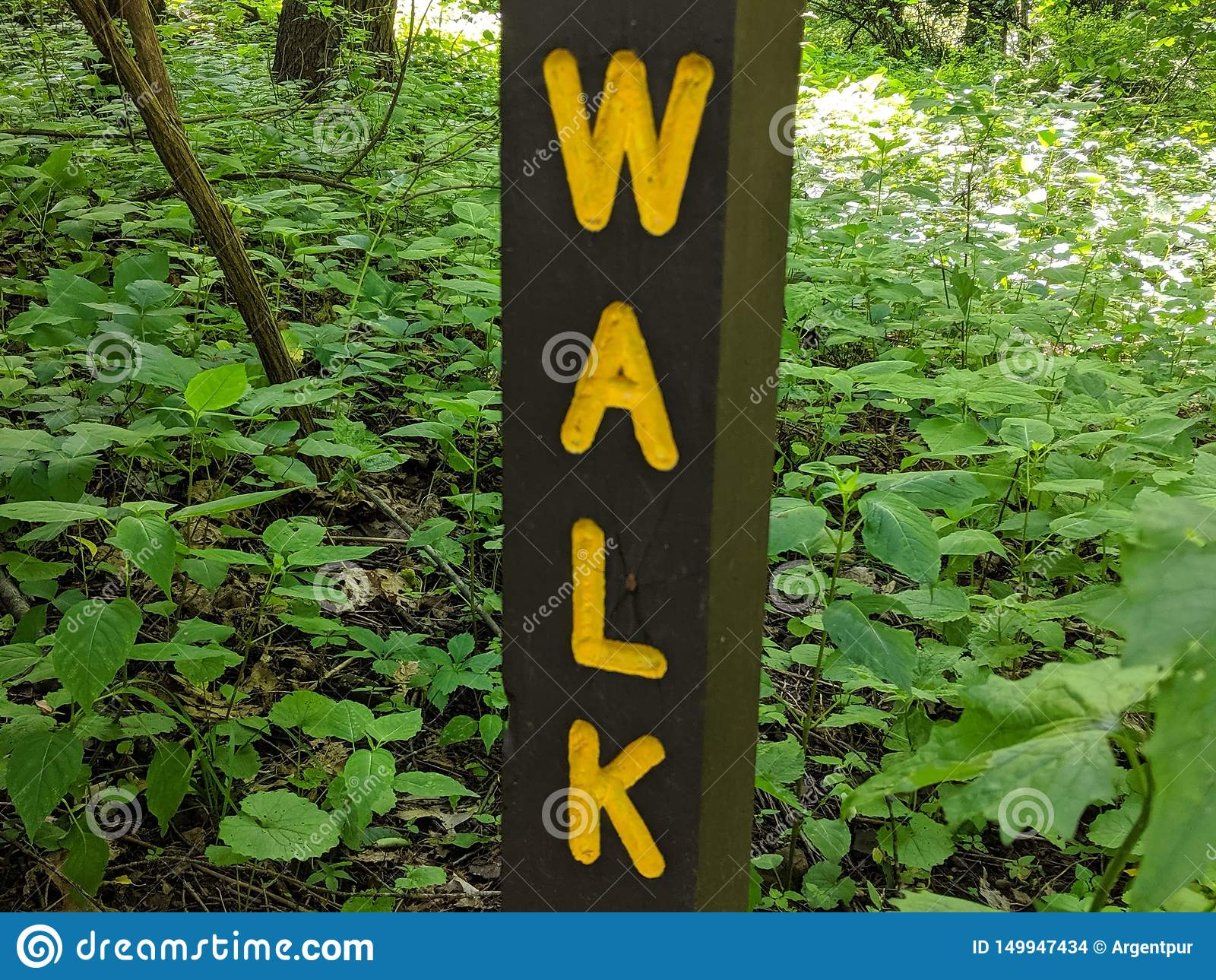 Walk sign, yellow letters on brown wood post