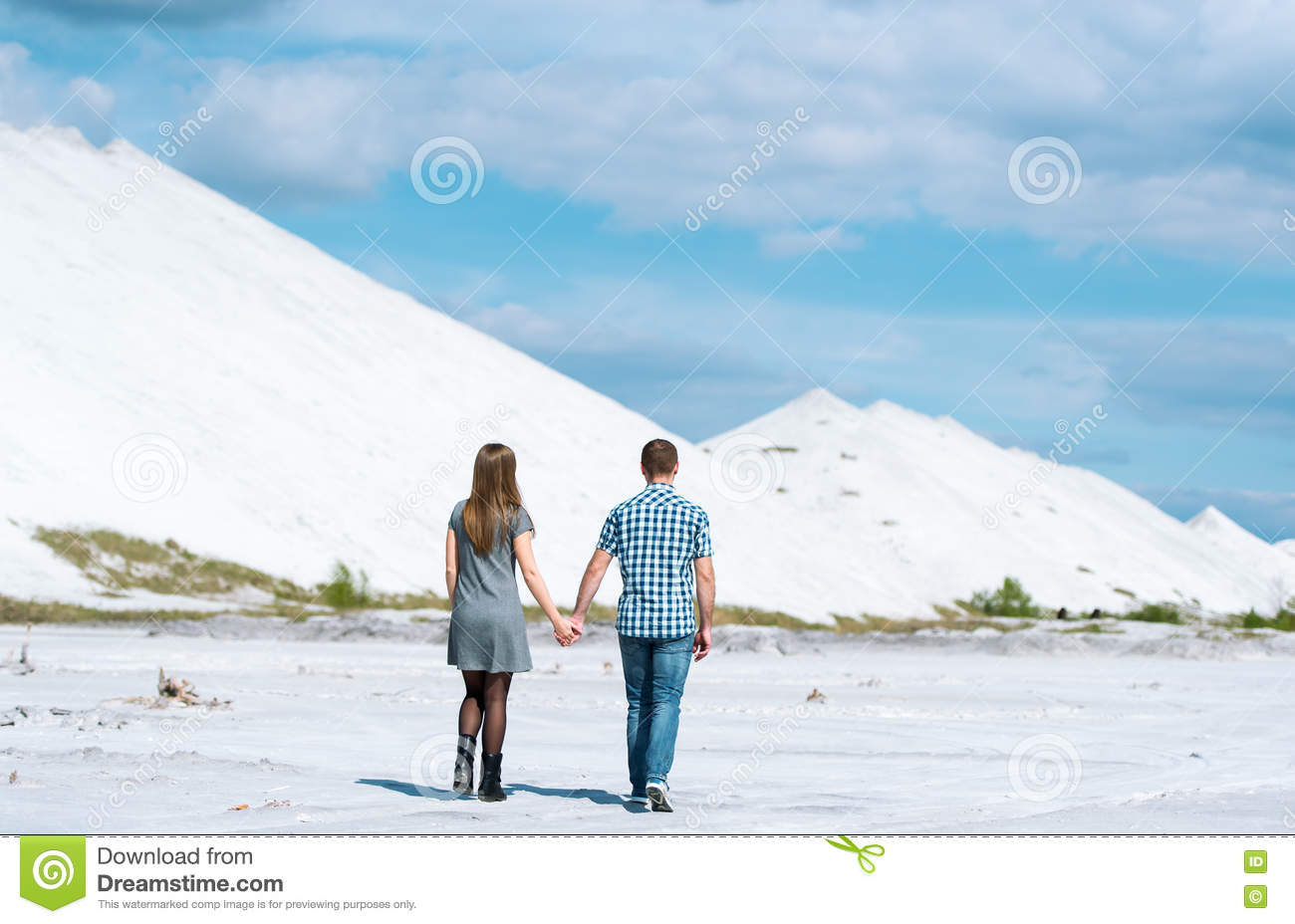 Walk of young couple on the desert earth.