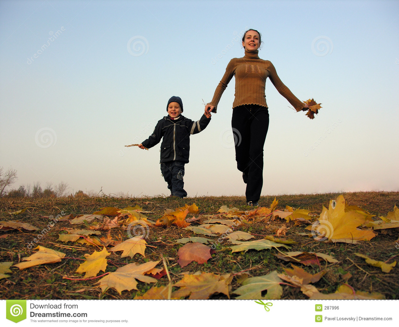 Walking mother with son on autumn leaves