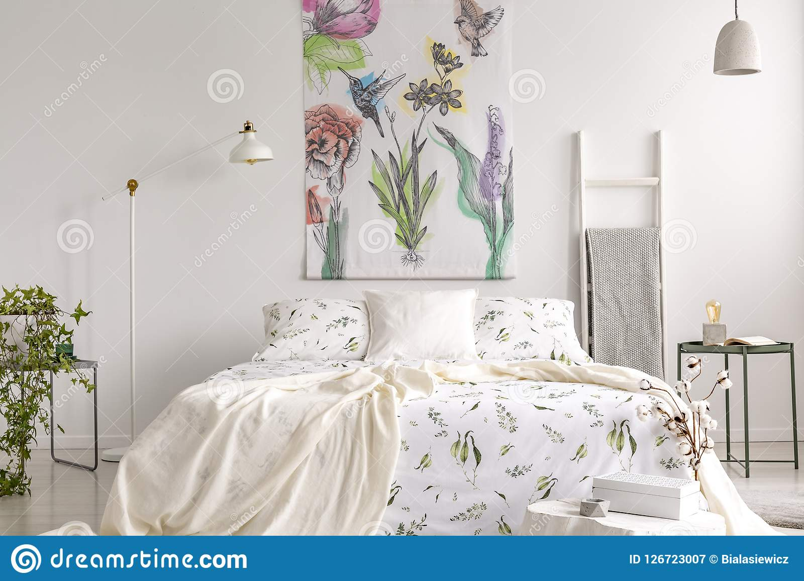 Wall Art Of Flowers And Birds Painted On A Fabric Above A Bed Which Is Dressed In Green Plants Pattern On White Bedding In A Fresh Stock Image Image Of Birds