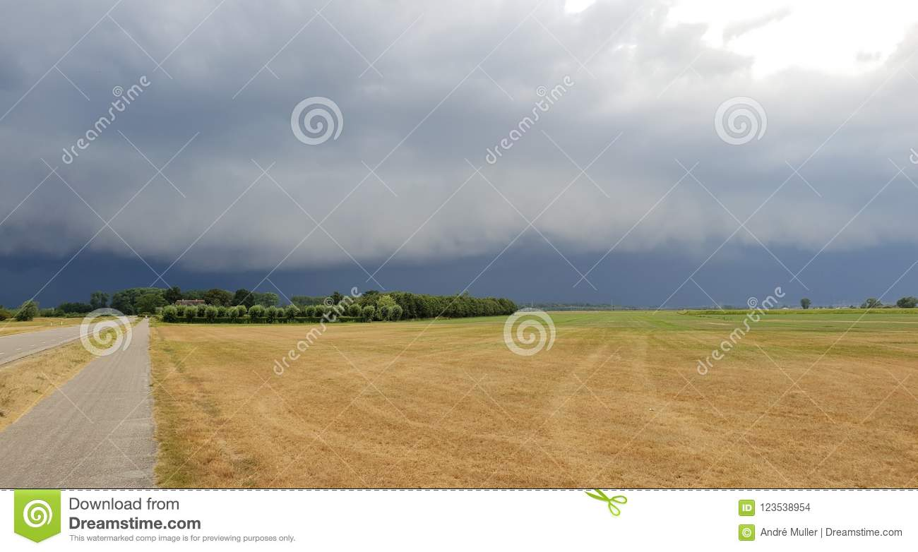 wall cloud of a thunderstorm above dry yellow fields and green trees in Laag Zuthem in Overijssel, the Netherlands.