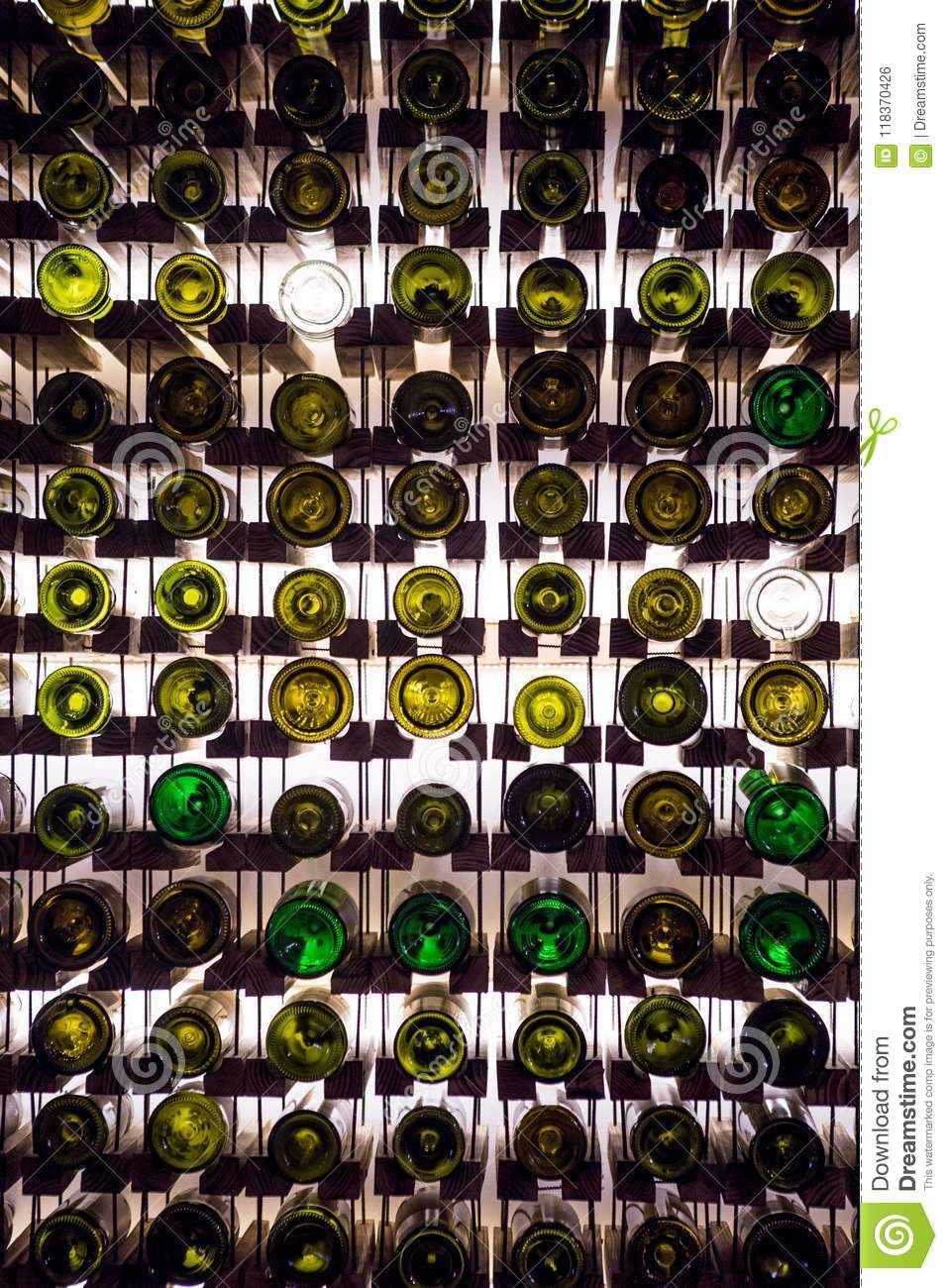 Wall of empty wine bottles. Empty wine bottles stacked-up on one another in pattern lit by the light coming from behind