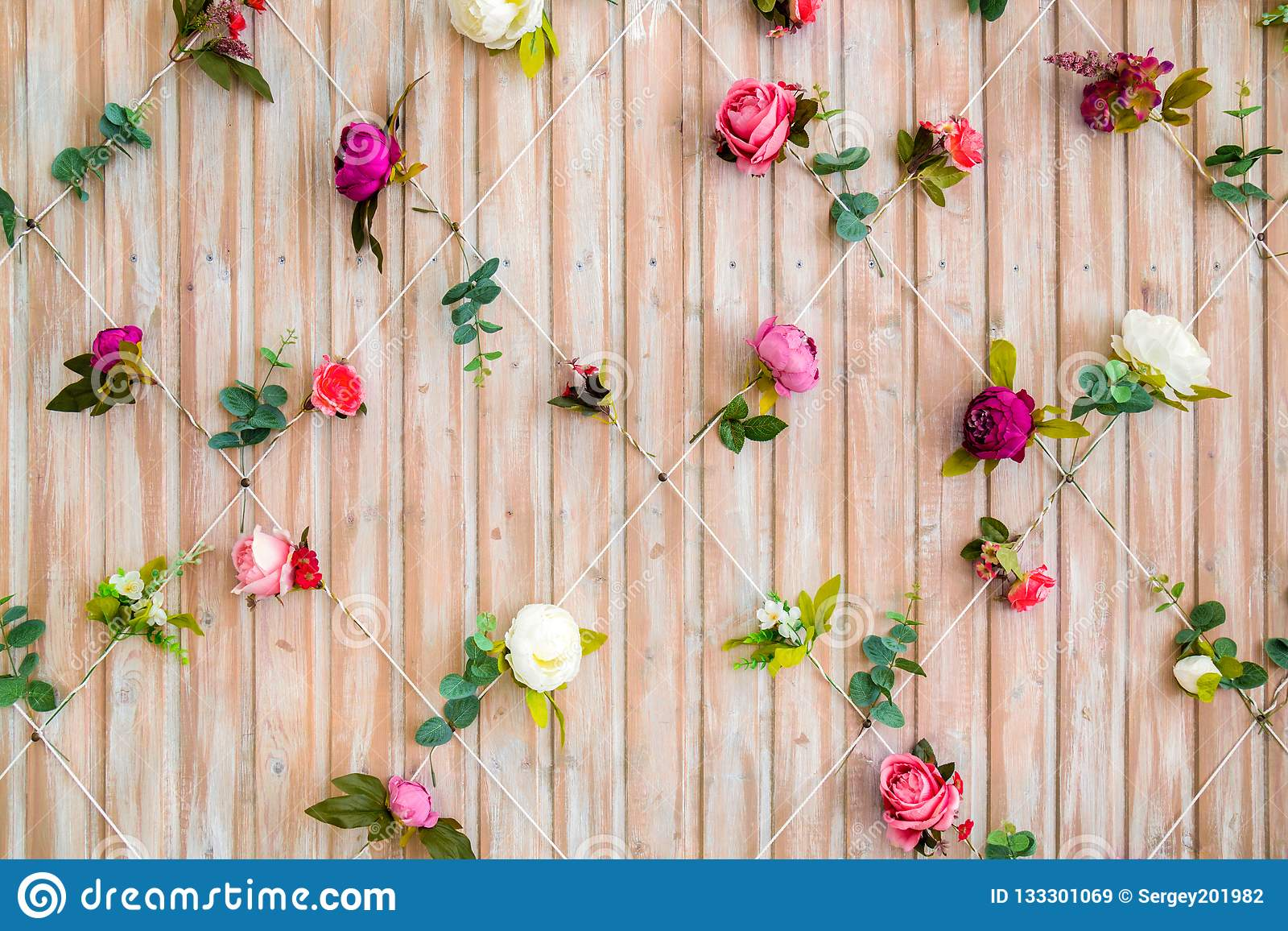 Wall of wooden boards decorated with flowers. Beautiful background for photo studio
