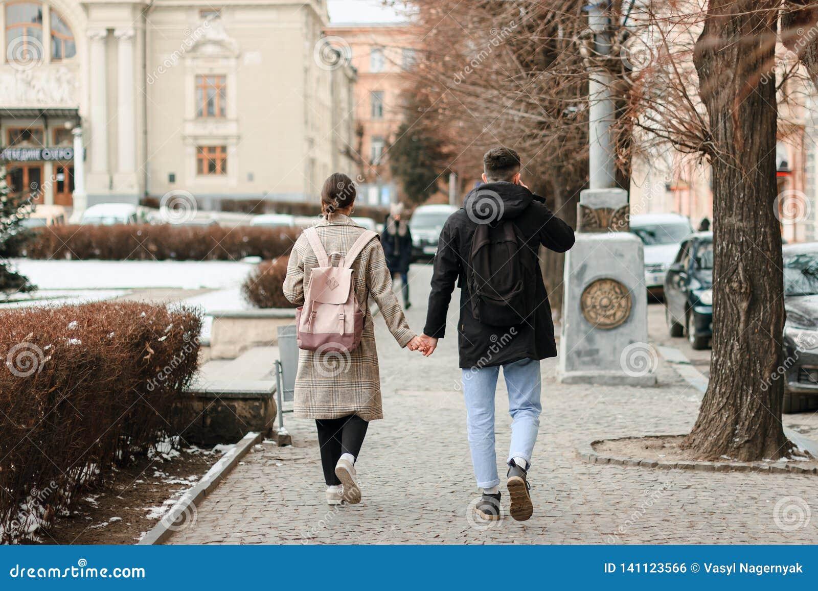 Wallking tillsammans Full längd av unga par på datumet som har gyckel tillsammans