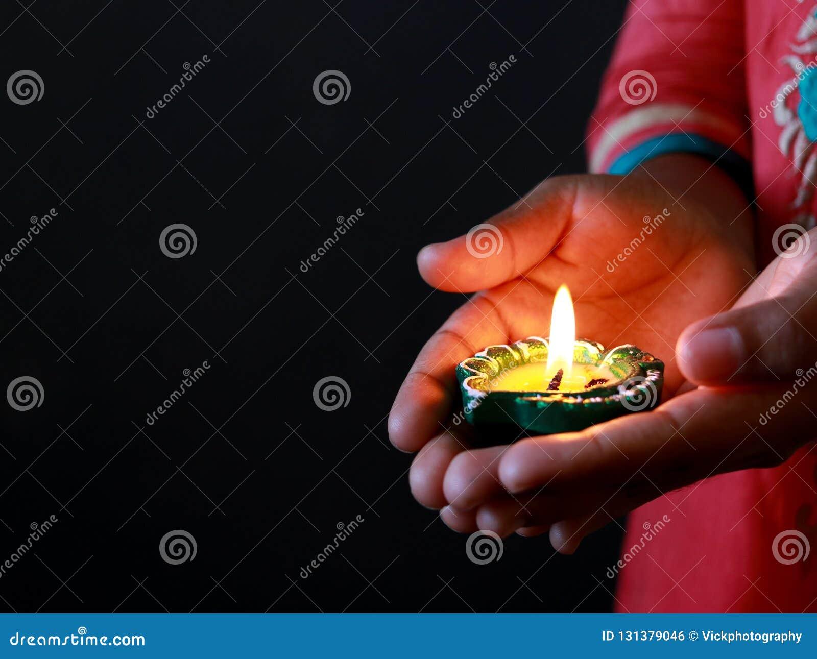 A Girl Holding Diya In Her Hand To Celebrate Diwali Stock