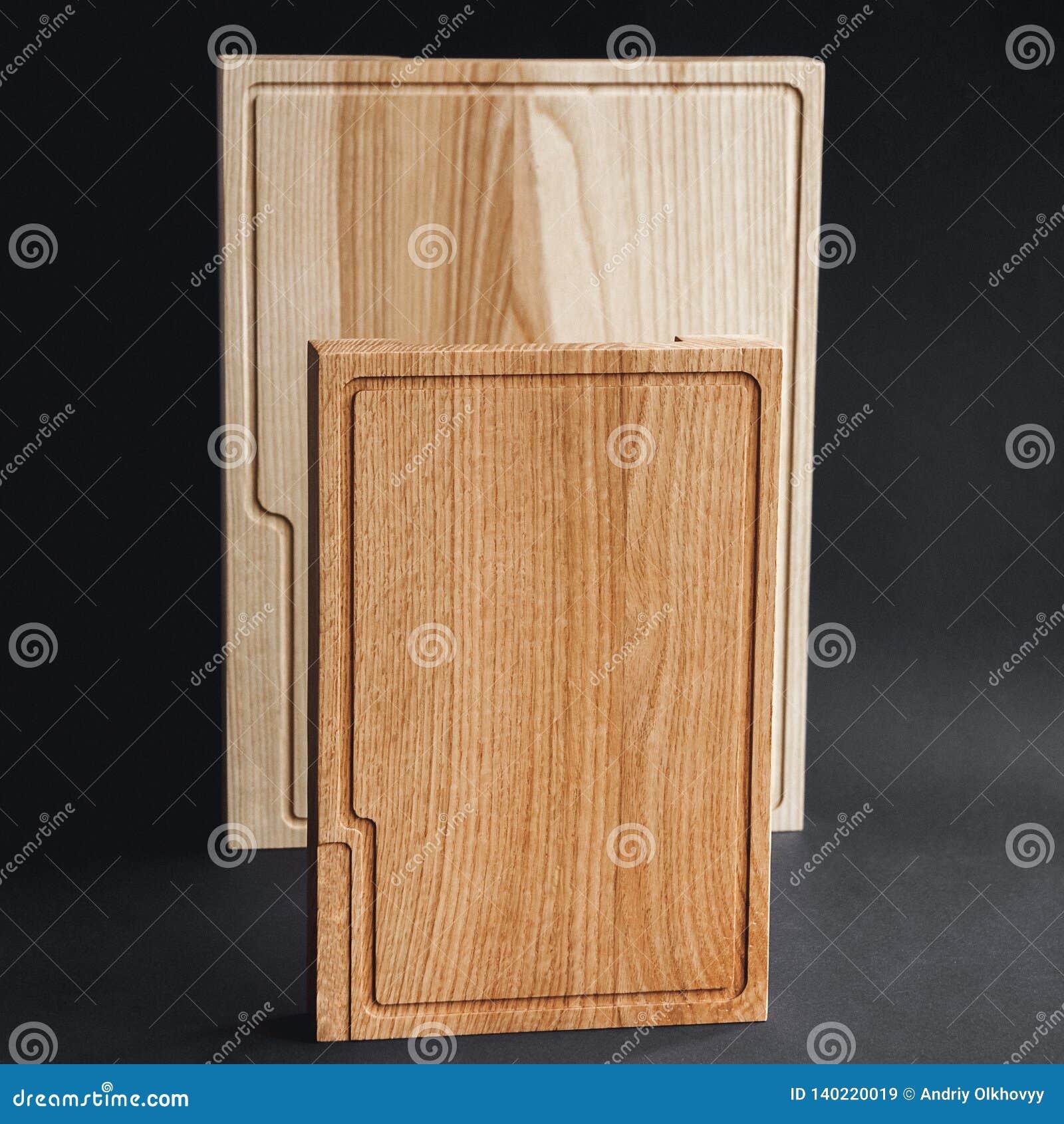 Walnut handmade wood cutting board on black wooden board