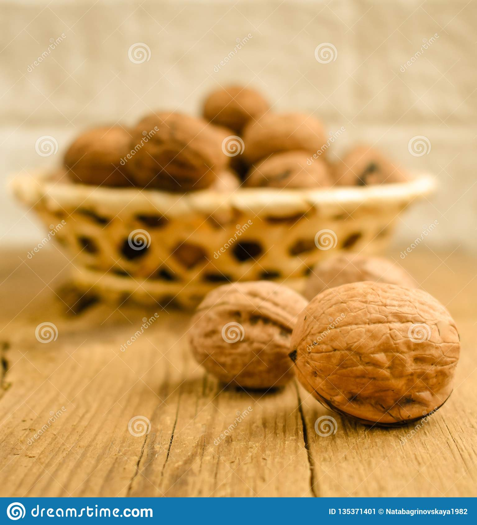 Walnuts in basket on wooden table