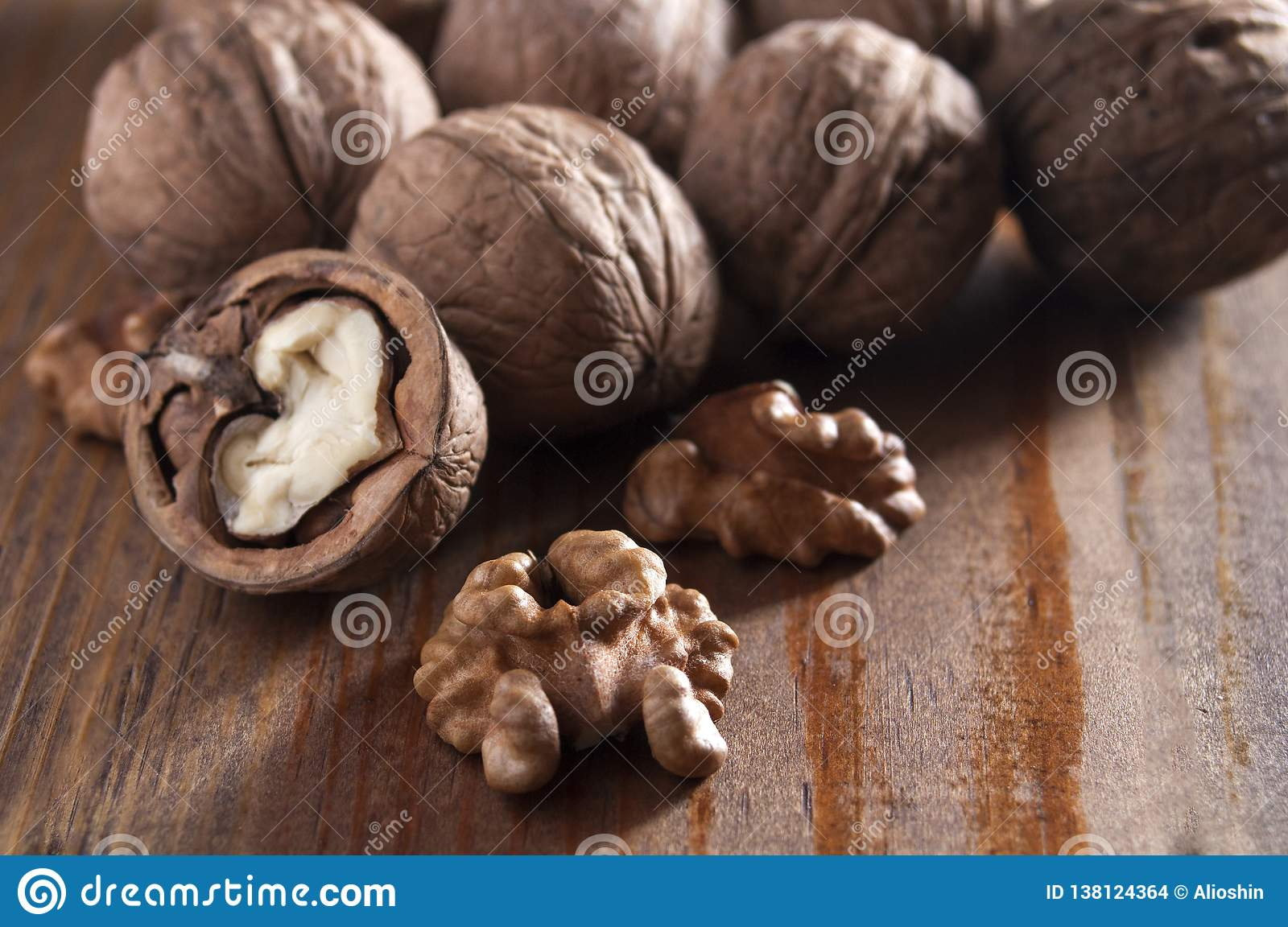 Walnuts peeled and inshell. Brown wooden background. Healthy nutrition, health care, diet. Healthy, fresh and nutritious food