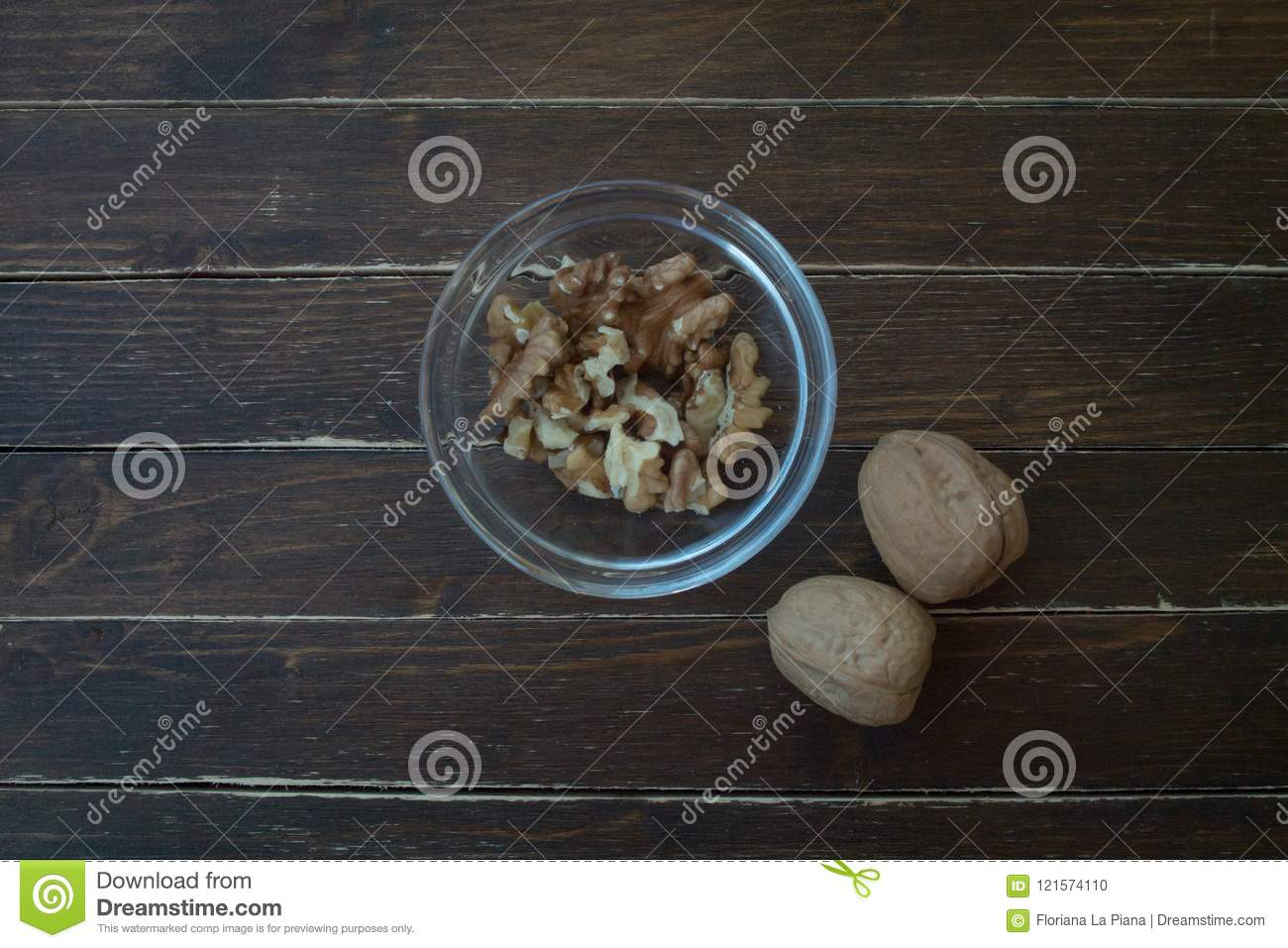 Walnuts in a transparent bowl on wood from above