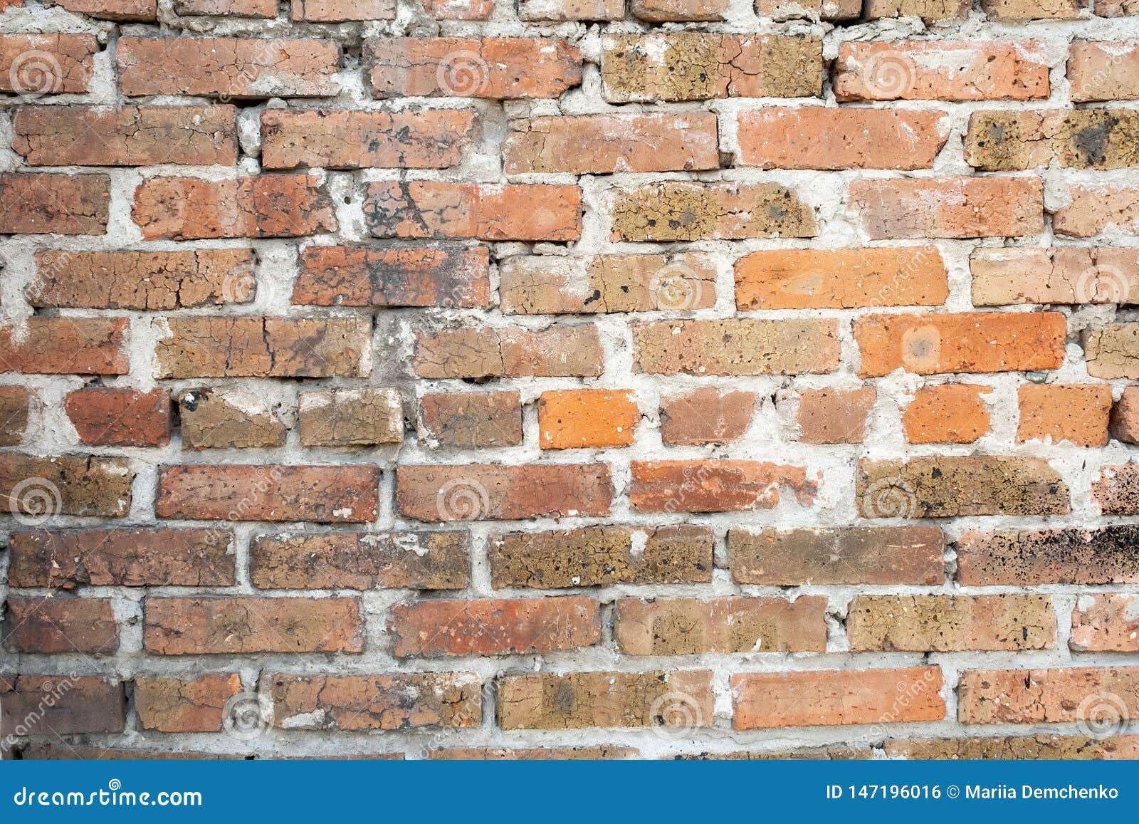 Wand des alten orange roten gebrochenen Ziegelsteines mit einer starken Schicht Zement zwischen ihnen