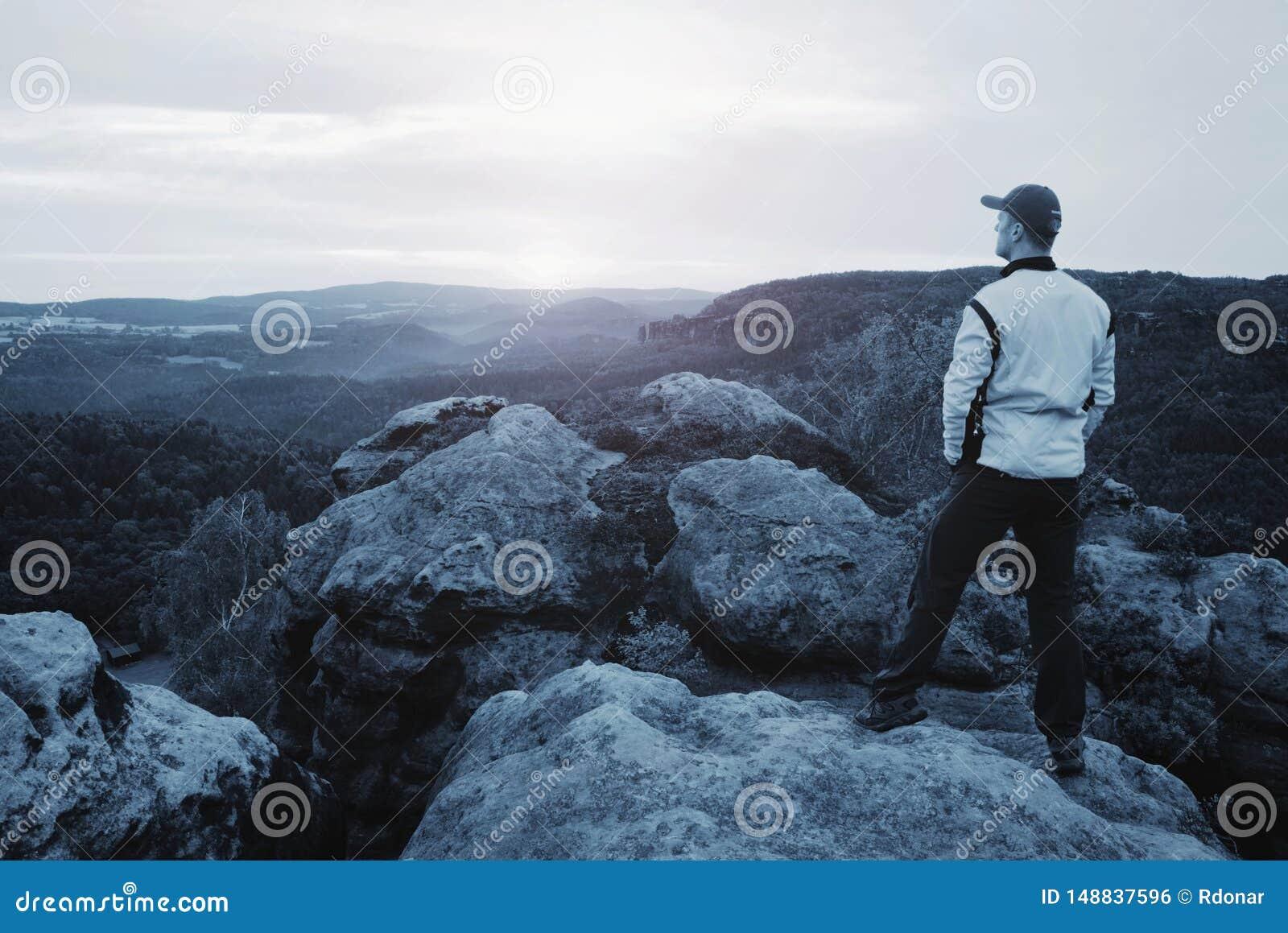 Wandelaar in sportieve kostuumtribune op piek in rots en horloge over mist