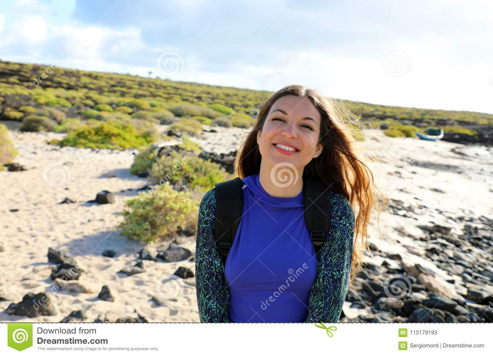 Wandelaarmeisje die bij camera in openlucht glimlachen Gelukkige jonge reizigersvrouw die Lanzarote heuvels en stranden in een zo