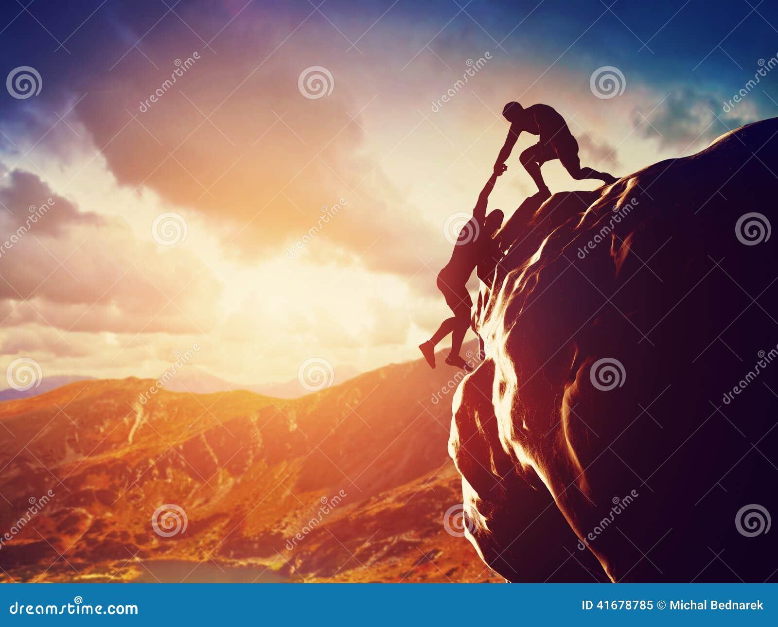 Wandelaars die op rots beklimmen, hand geven en helpen te beklimmen