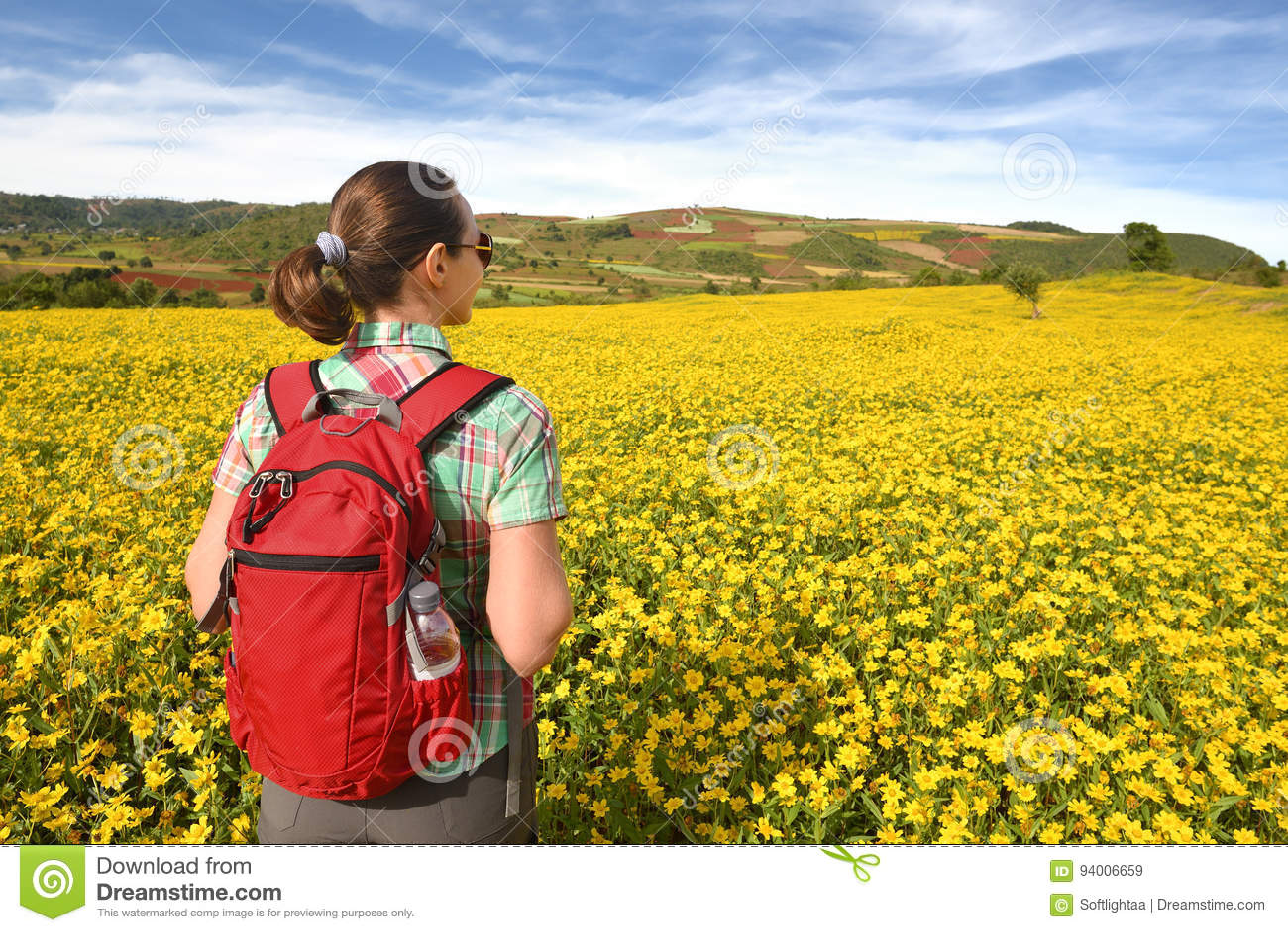 Wanderer mit Rucksack gehend durch Wiese auf Hintergrund von colo