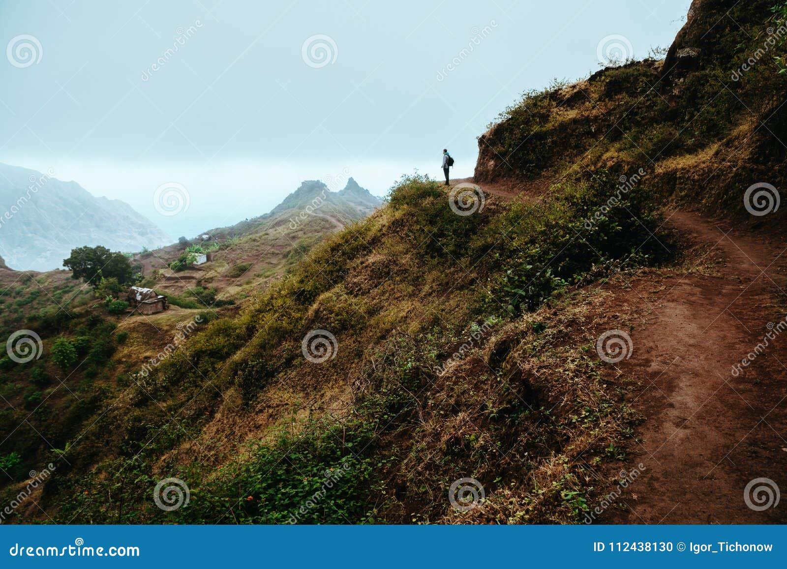 Wandererschattenbild untersucht das Tal und hört auf die Ruhe Nebel und Nebel hängen über den Bergspitzen auf