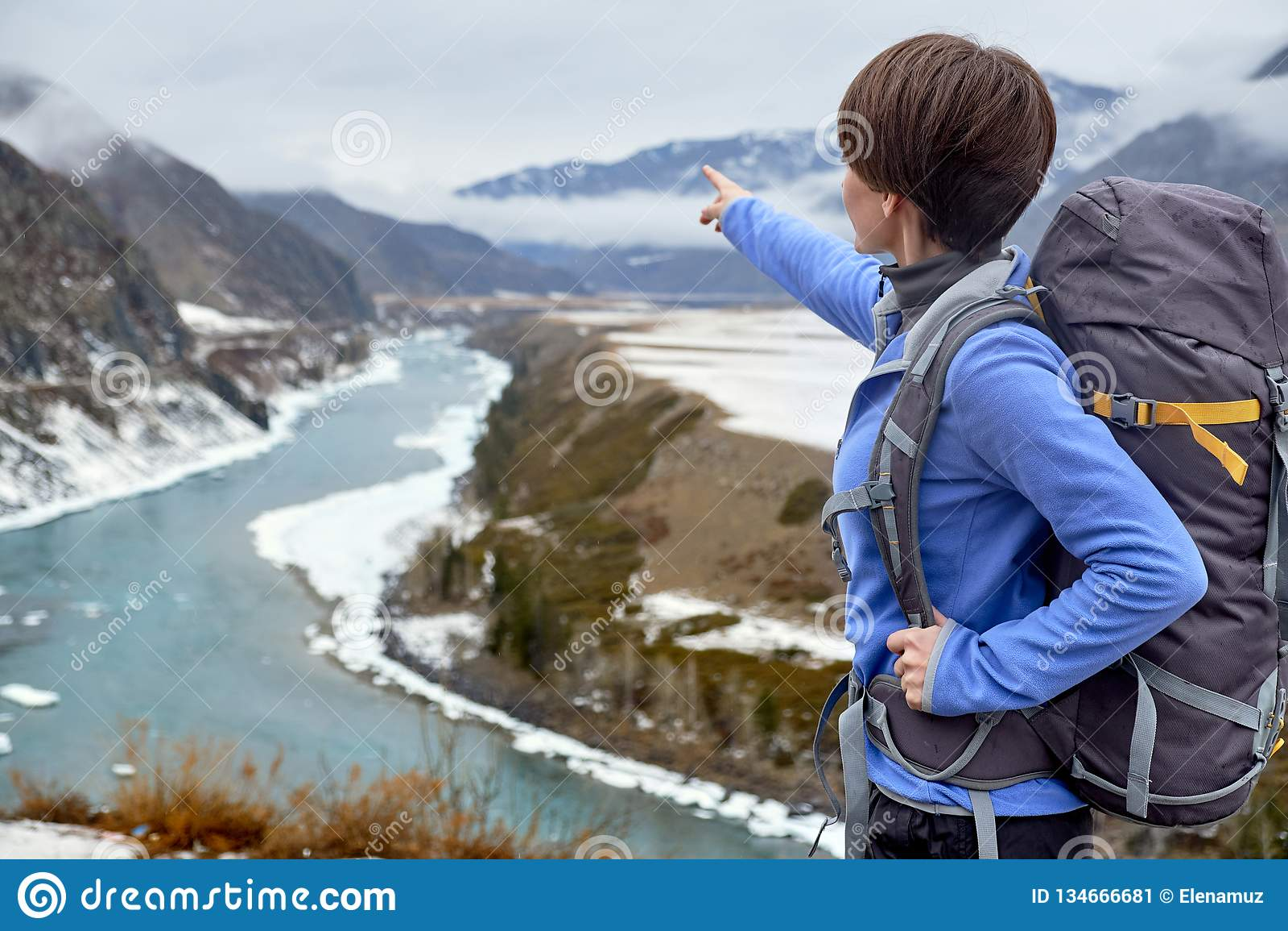 Wandern der lächelnden Frau mit einem Rucksack in den Bergen Schönes junges Mädchen reist in die Berge