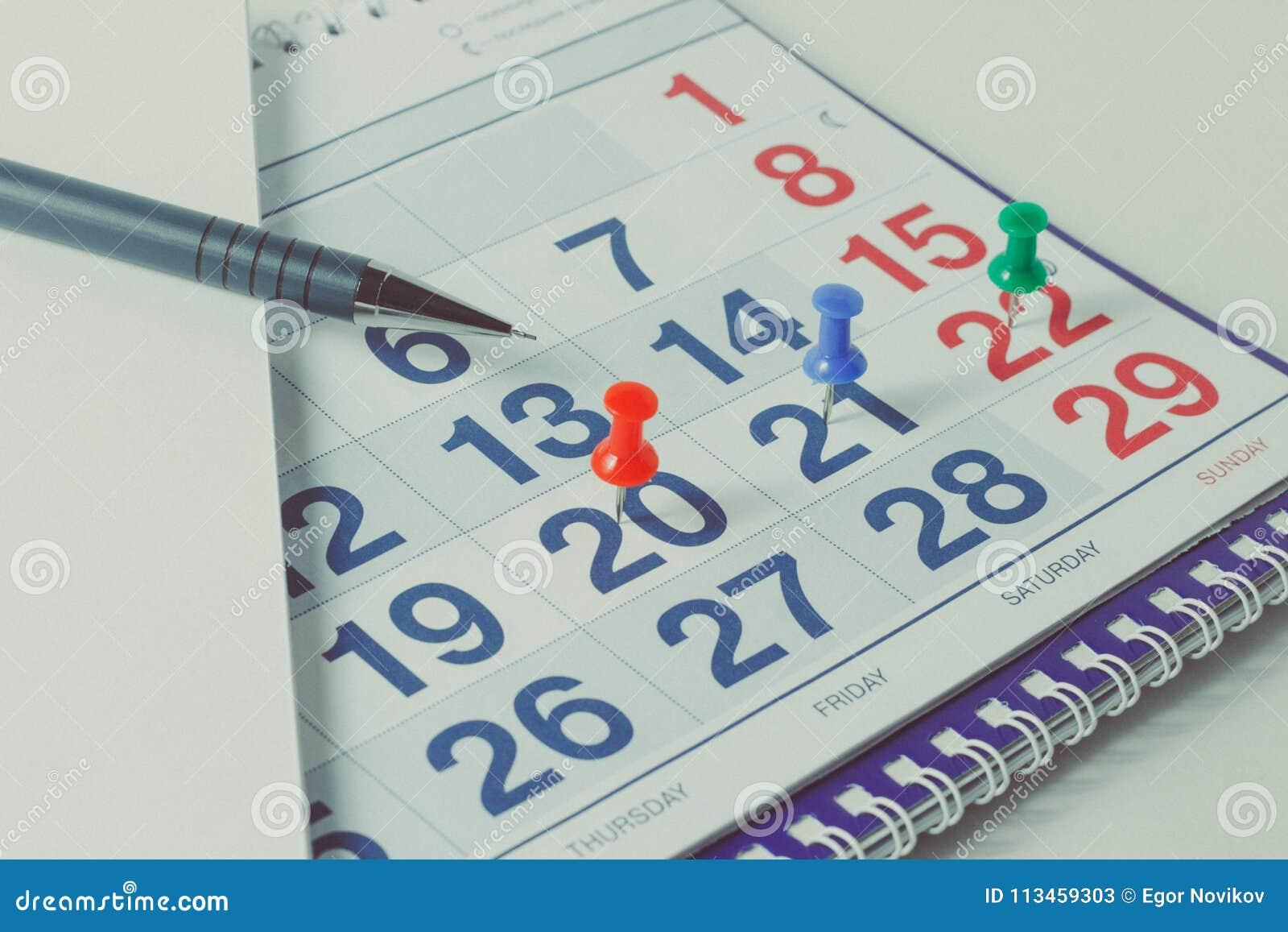 Wandkalender und Stift, wichtige Tage werden mit knops markiert