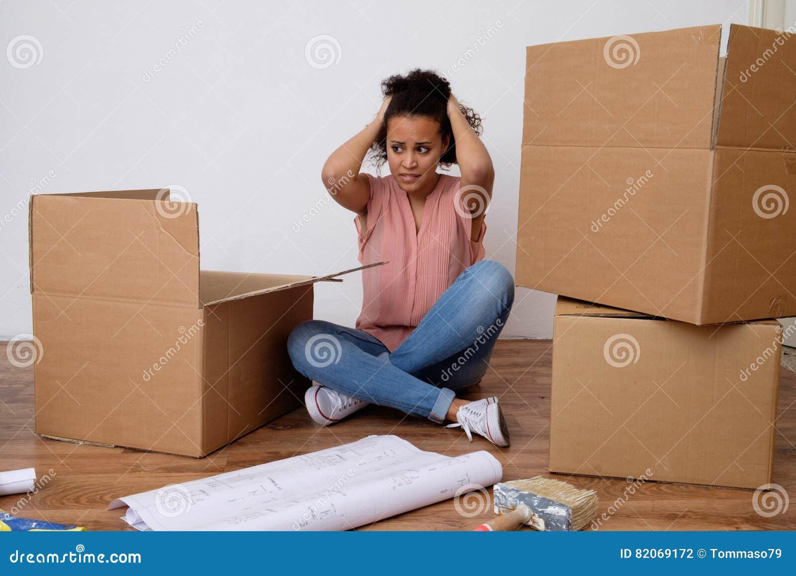 Wanhopige en vermoeide vrouw tijdens huisverhuizing