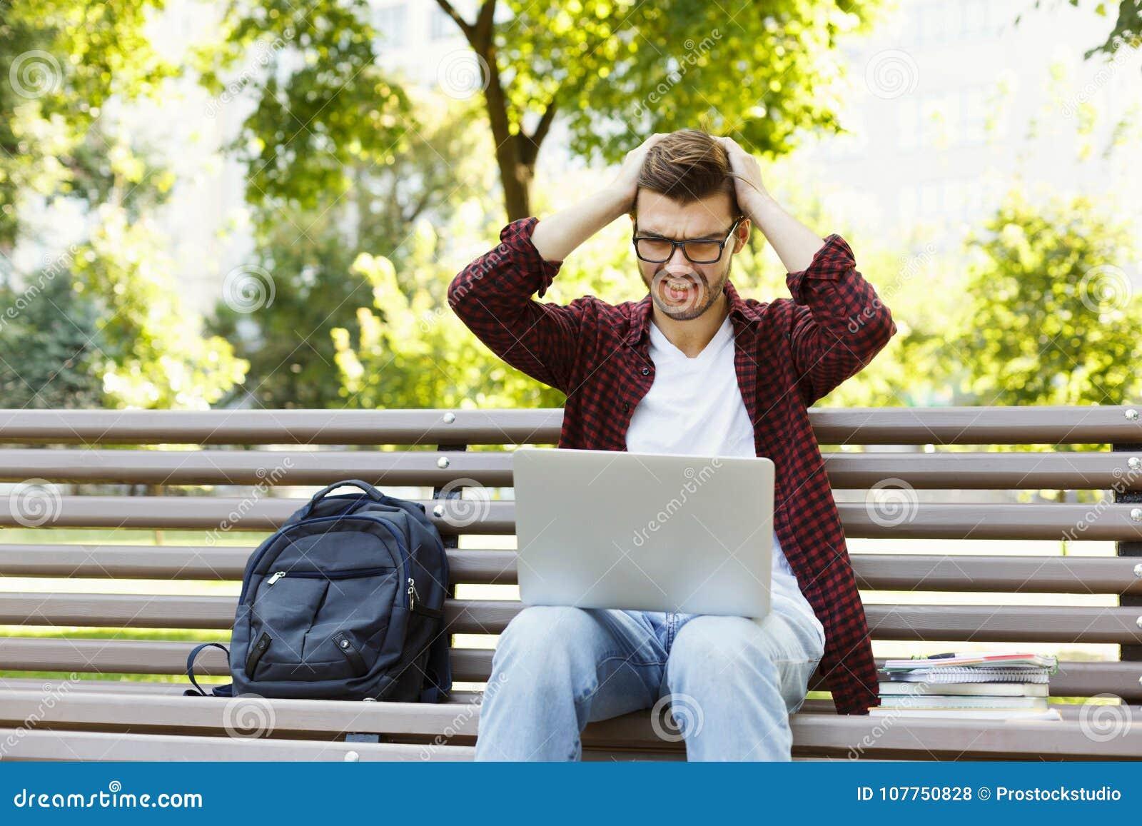 Wanhopige jonge mens die laptop in openlucht met behulp van