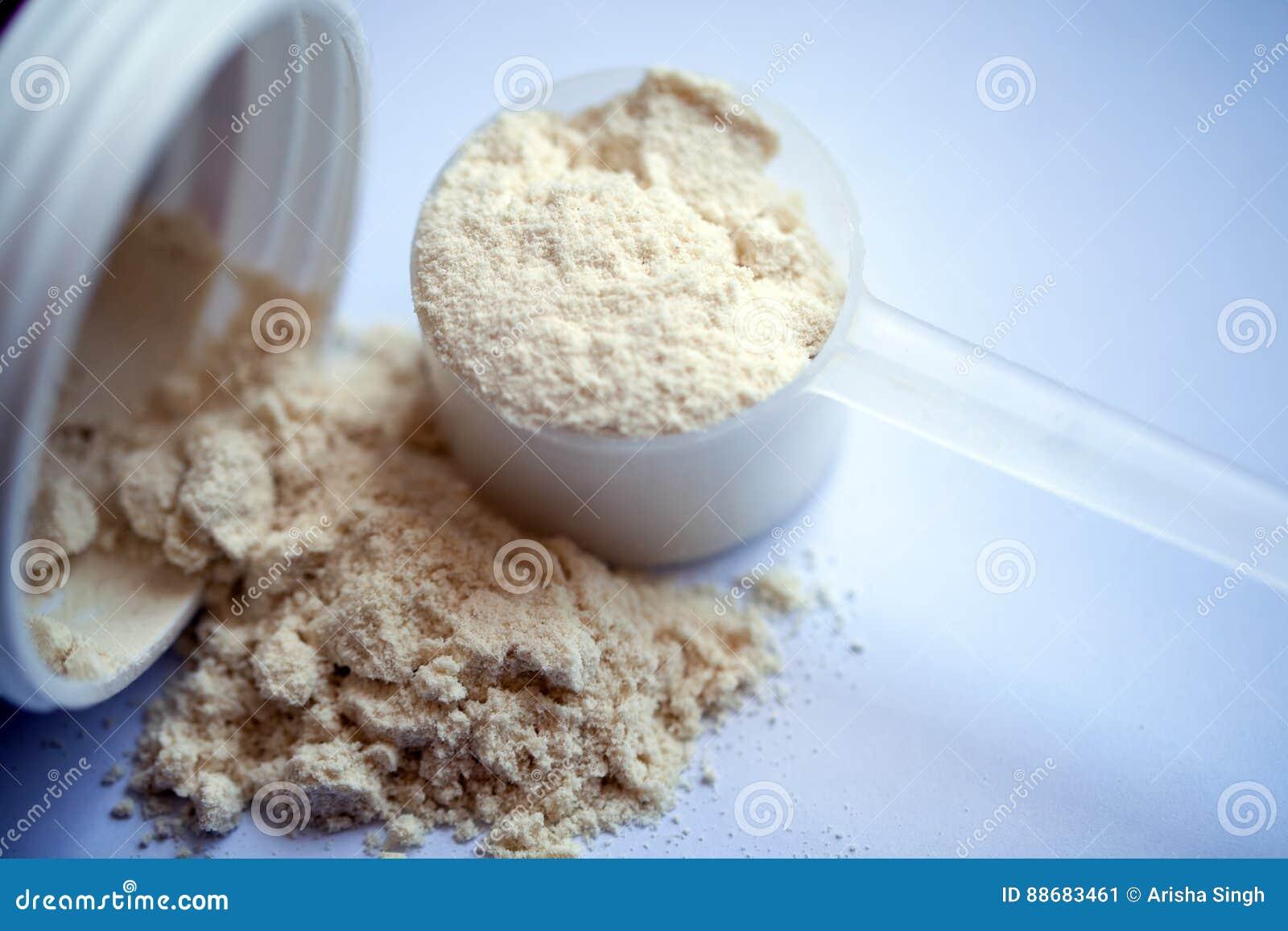 Waniliowy proteina proszek w miarce na białym tle