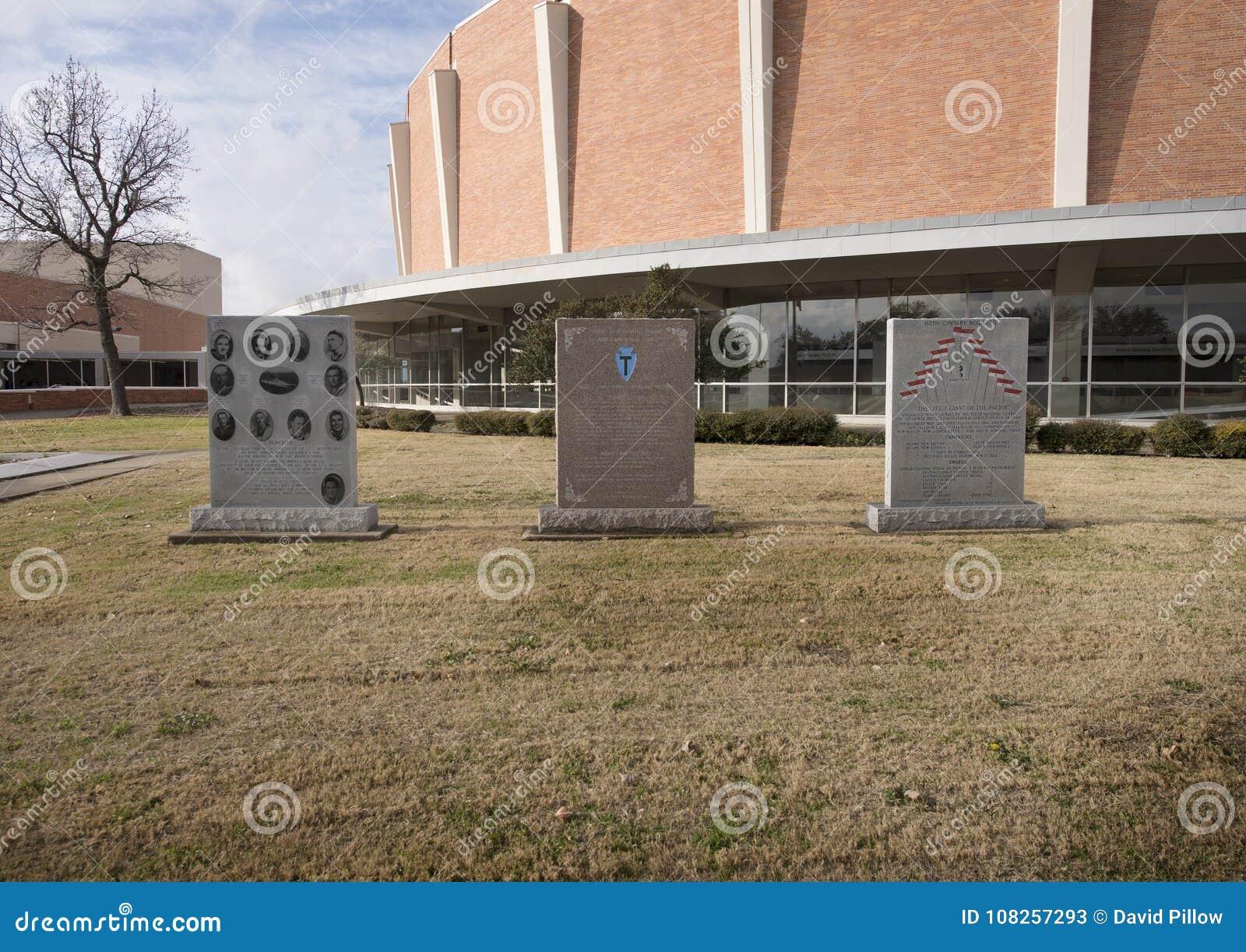 War monuments in the Veterans Memorial Garden with Dallas Memorial Auditorium in the background.