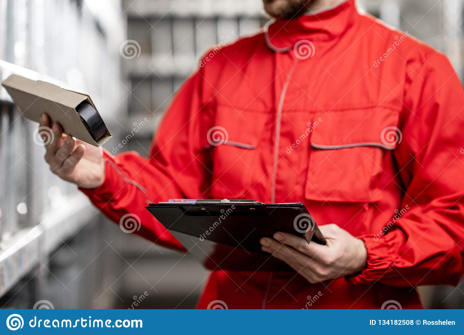 Warehouse worker with clipboard in the storage