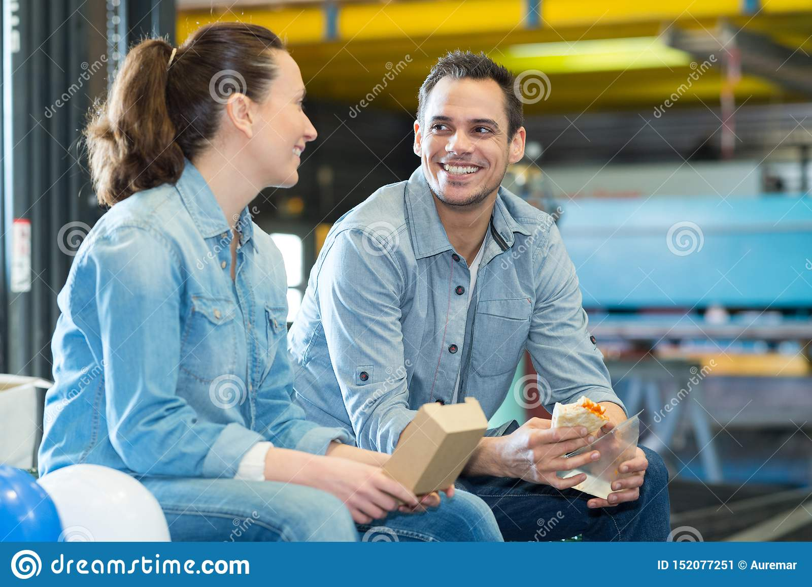 Warehouse workers sitting on pallets for lunch break