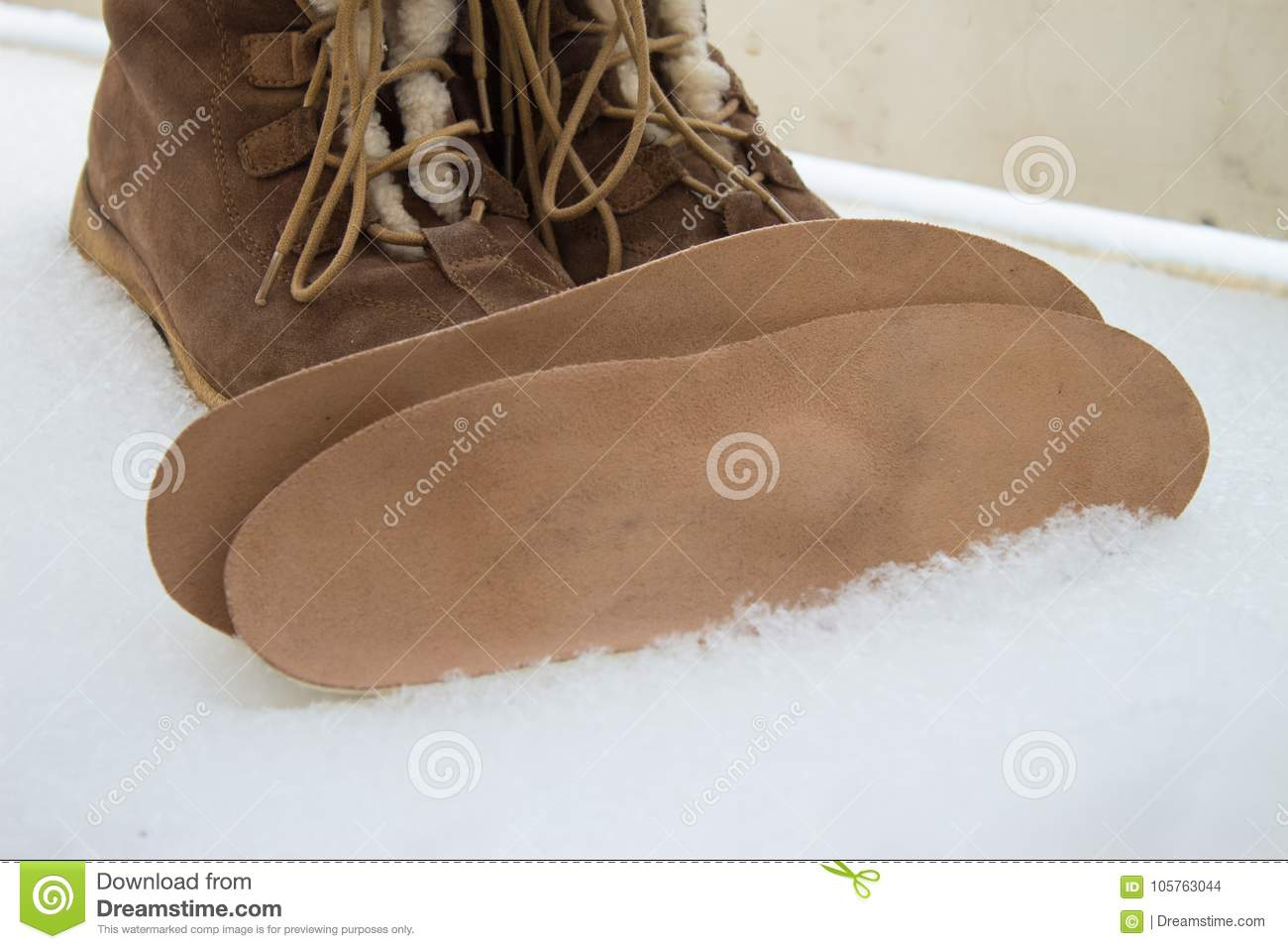 Warm brown shoes and orthopedic insoles. Winter background, foot