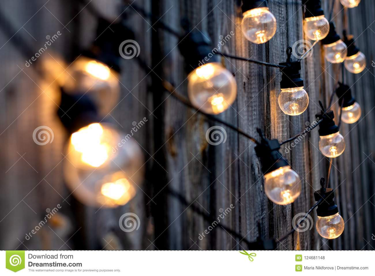 Warm color LED light bulbs on old wooden background in the garden, copyspace, outdoor lighting deciration concept