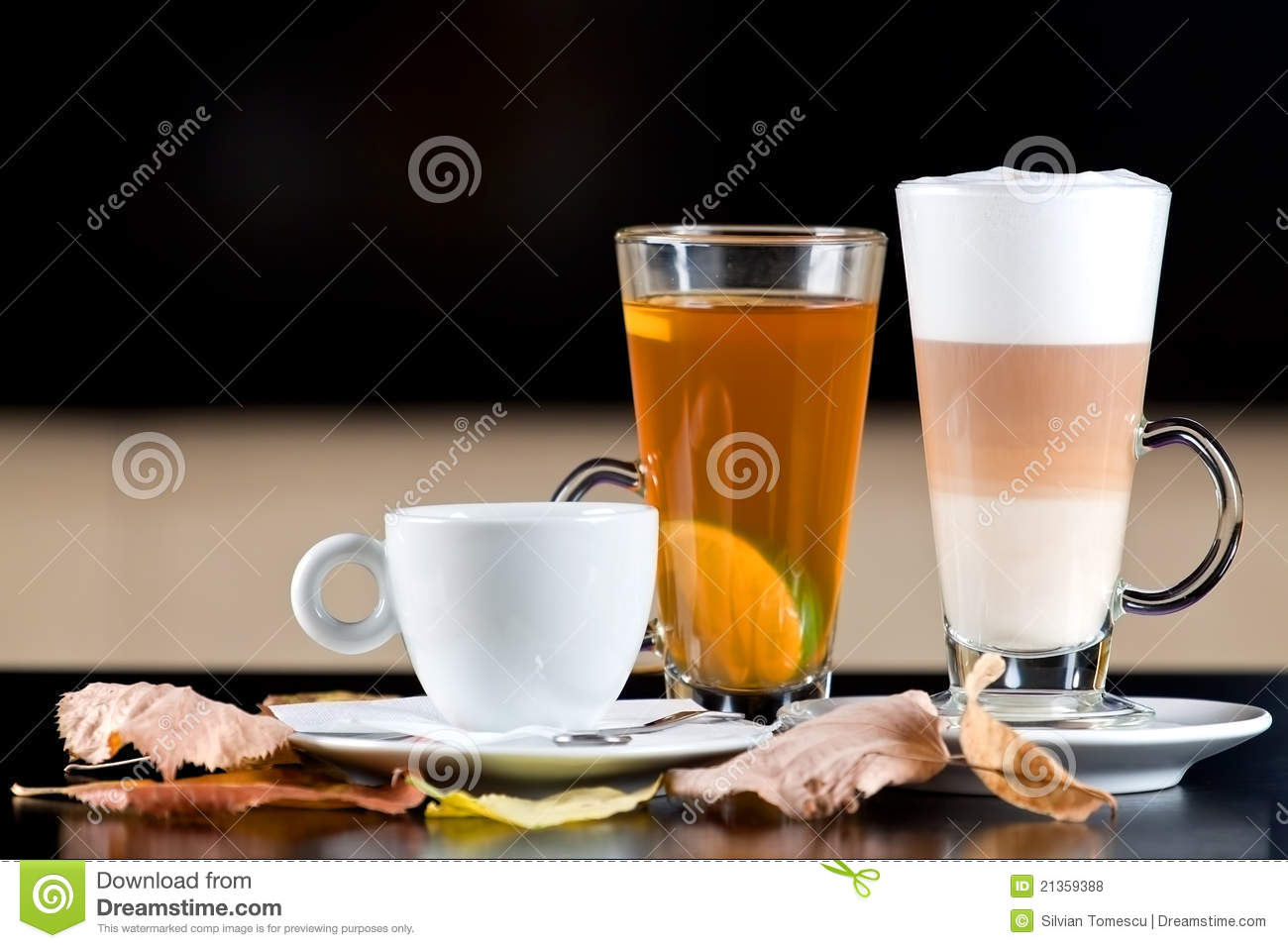 d3926686c83 Cup of coffee, glass of fruit tea and latte on black wood table with autumn  leaves. Selective focus and space for text in the left.