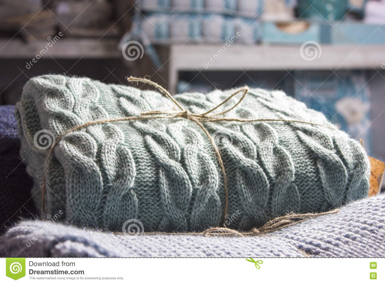 Warm knitted blankets folded stack. Plaid mint color over blue h