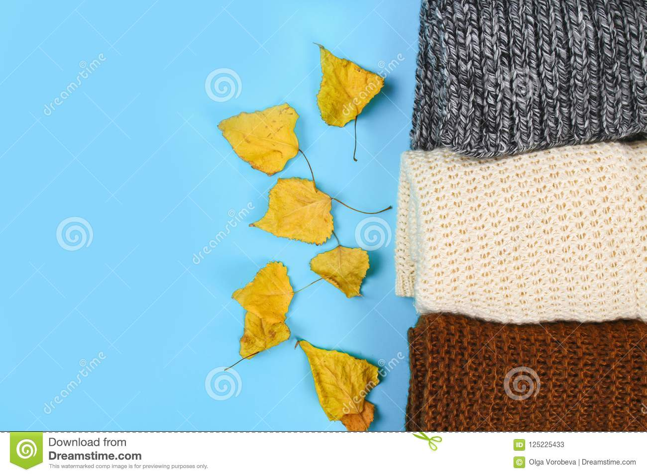 373f36baa4 Warm Knitted Sweaters. Pile Of Knitted Clothes On Blue Background ...