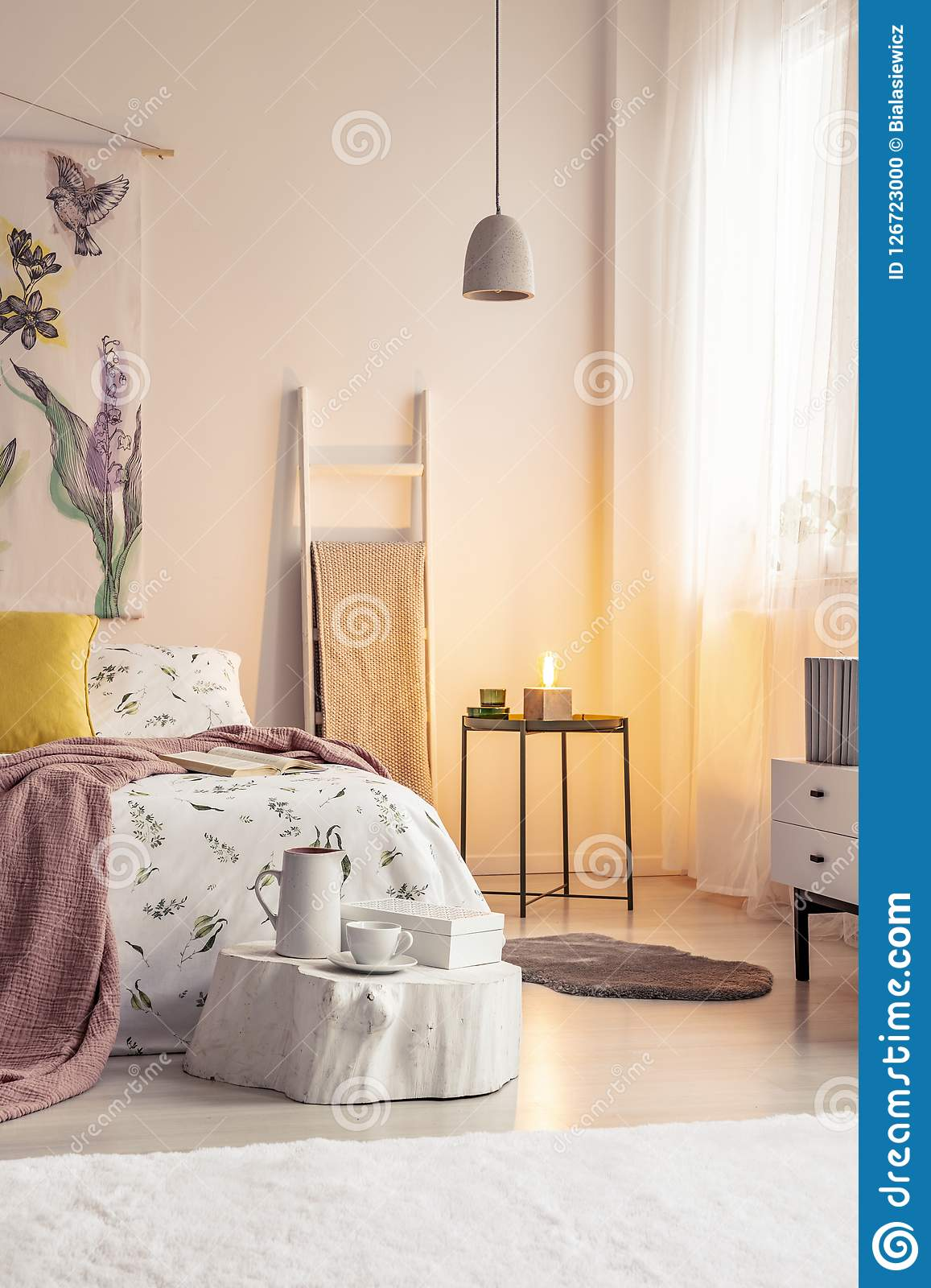 Warm lamp light in a soft colors bedroom interior with a bed dressed in bedding, cushions and blanket. Painted material art on the