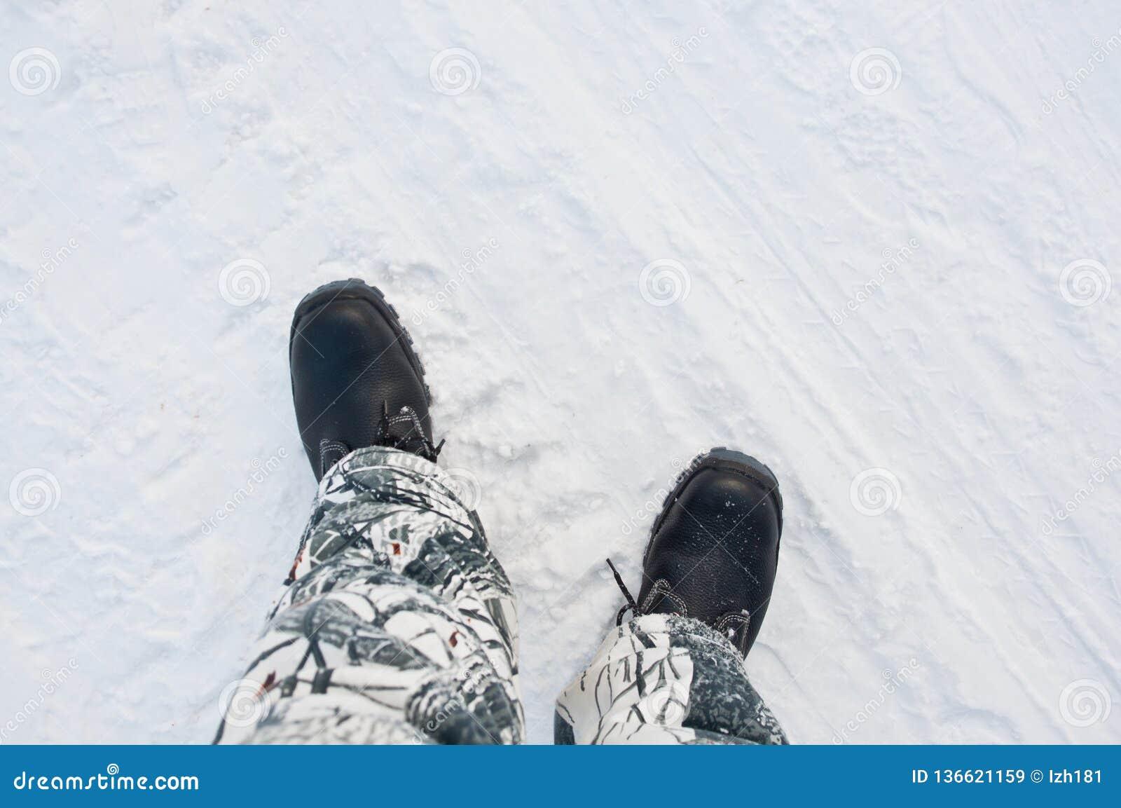 Warme het werklaarzen op de achtergrond van een sneeuwweg