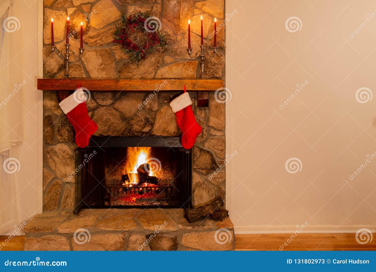 Warme open haard met kroon, candelabras en twee Kerstmiskousen in het familiehuis