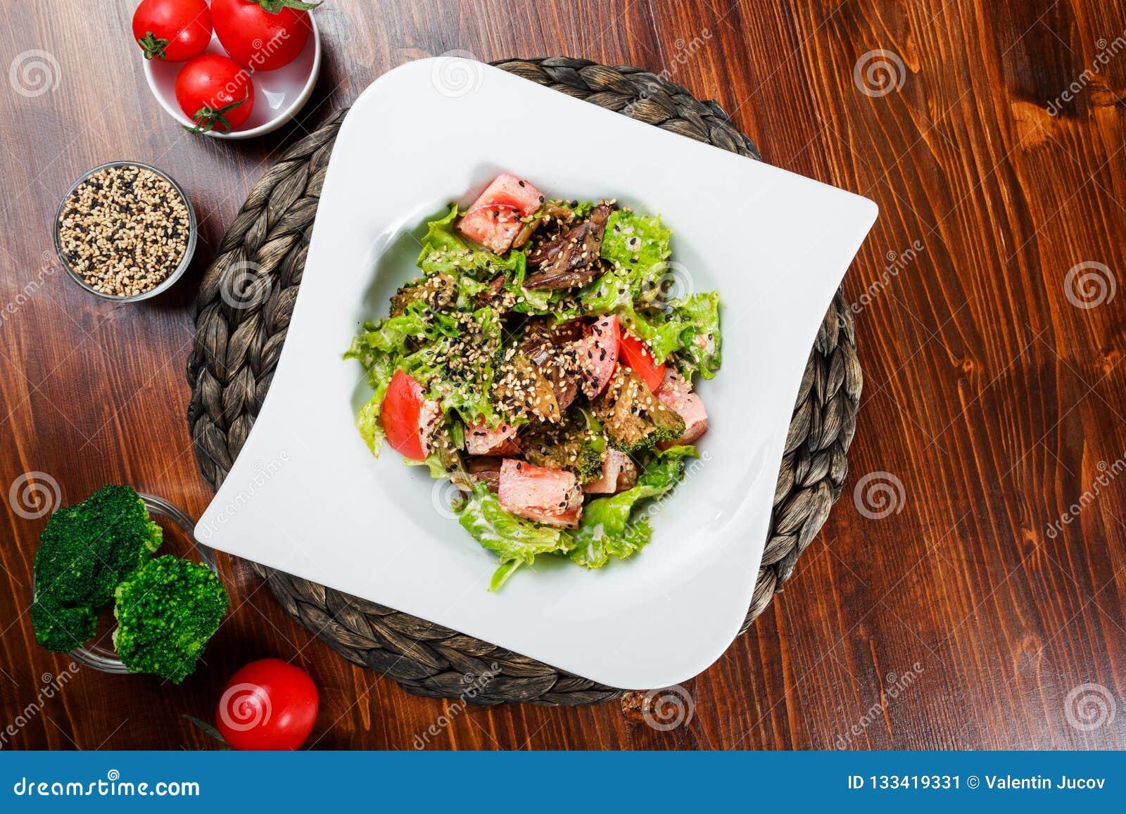 Warme salade met kippenlever, tomaten, slabladeren, broccoli op houten lijst