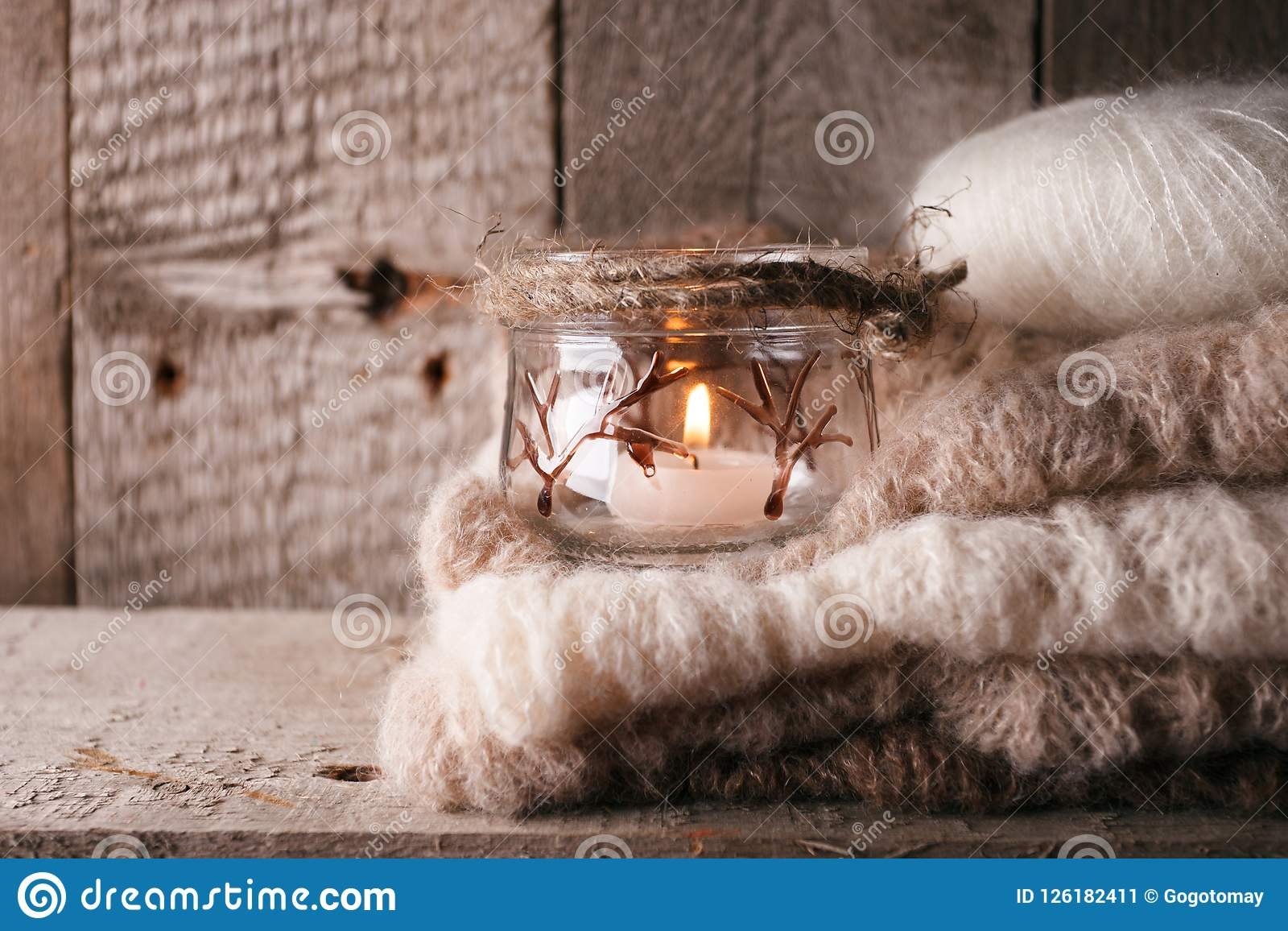 Warme Strickjacke auf hölzerner rustikaler Bank, Kerze, gemütliche alltägliche Szene der Ruhe Fallherbstwochenende Einfarbiges Ko