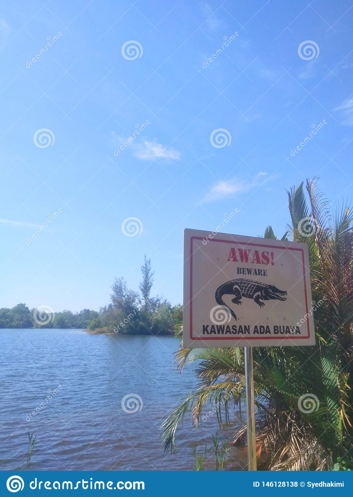 sign board image of a crocodile and a lake