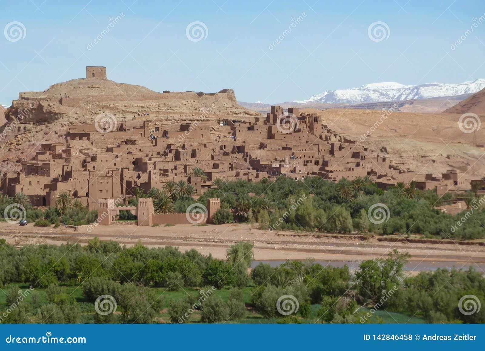 Warowny miasto Ait Benhaddou wzdłuż poprzedniej karawanowej trasy między Marrakech w Maroko z śniegiem i Sahara zakrywał atlant