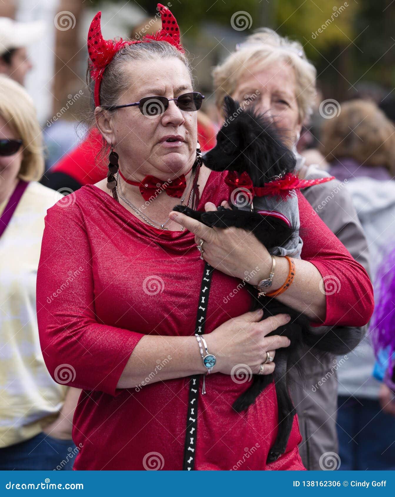 Warrenton, Virginia/USA-10/28/18: Donna vestita come un diavolo che tiene un cane alla parata di Halloween Happyfest in Città Vec