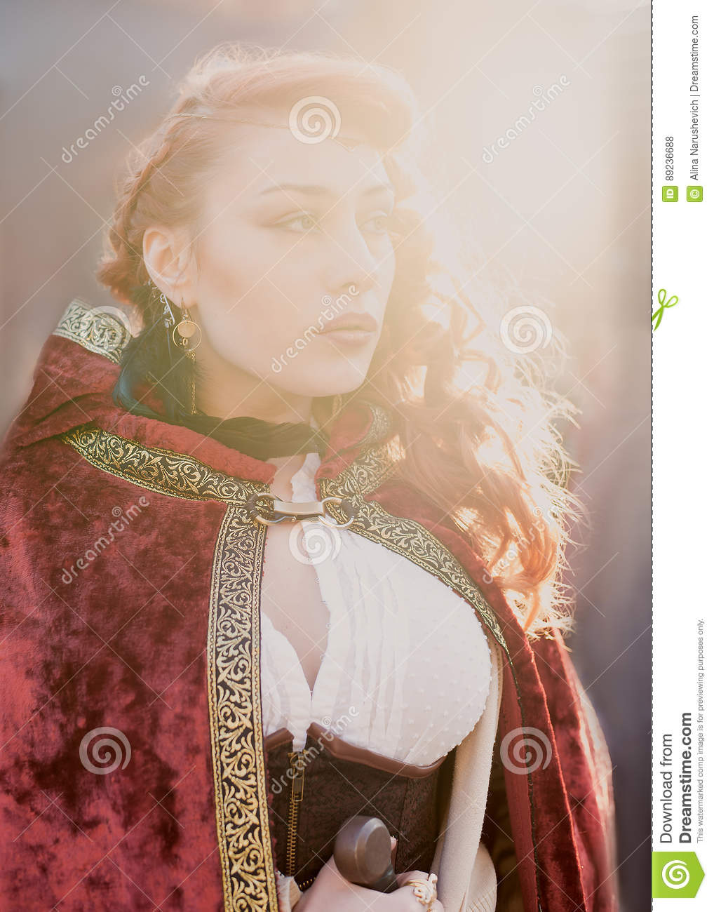 Warrior woman with sword in medieval clothes in sun light