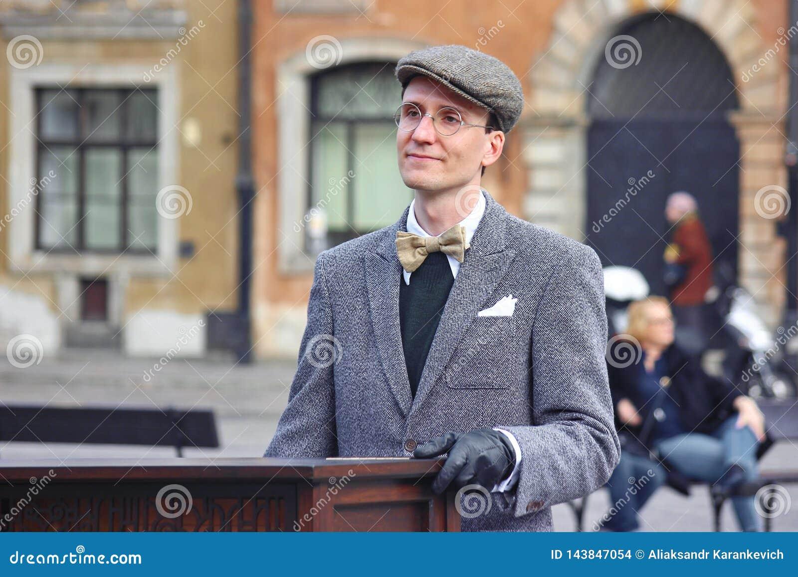Warszawa, Polska 03 22 2019 - gracz na lufowym organie hurdy-gurdy w kwadracie w starym mieście lub W szkłach mężczyzna